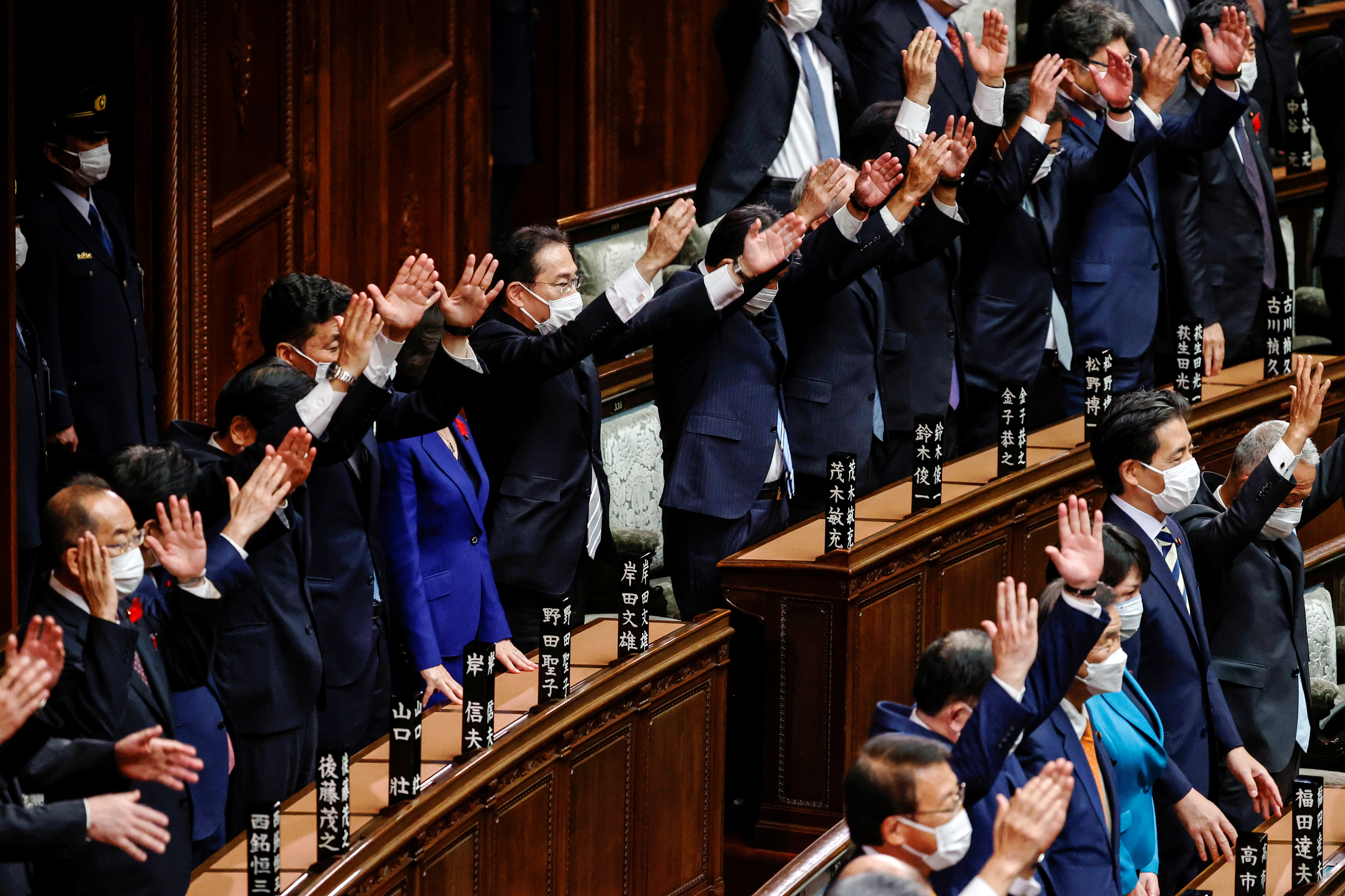 Japan's Prime Minister and the leader of the ruling Liberal Democratic Party (LDP) Fumio Kishida and his cabinet ministers raise their hands and shout