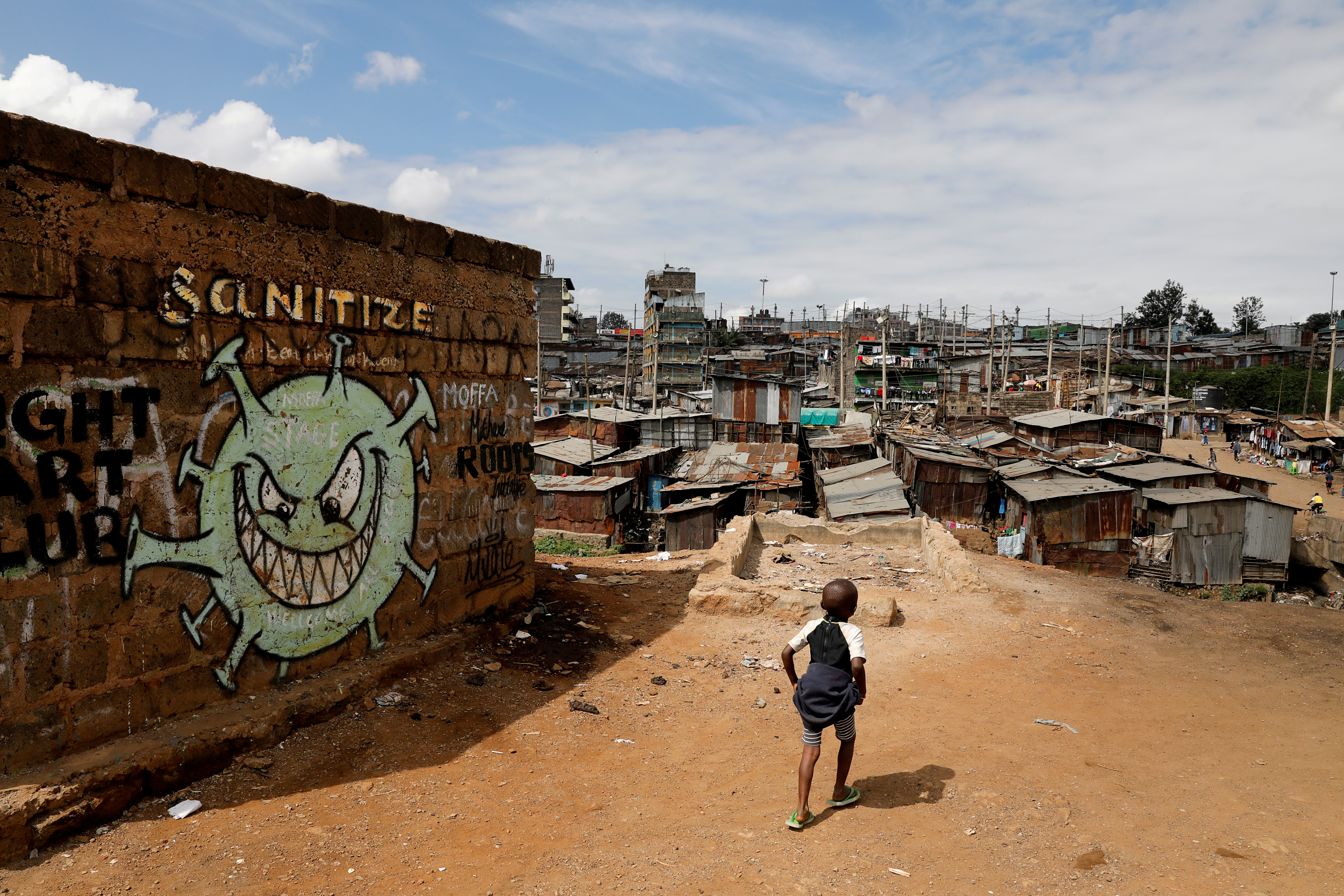 A boy walks in front of a graffiti promoting the fight against the coronavirus disease (COVID-19) in the Mathare slums of Nairobi, Kenya, May 22, 2020.  REUTERS/Baz Ratner/File Photo