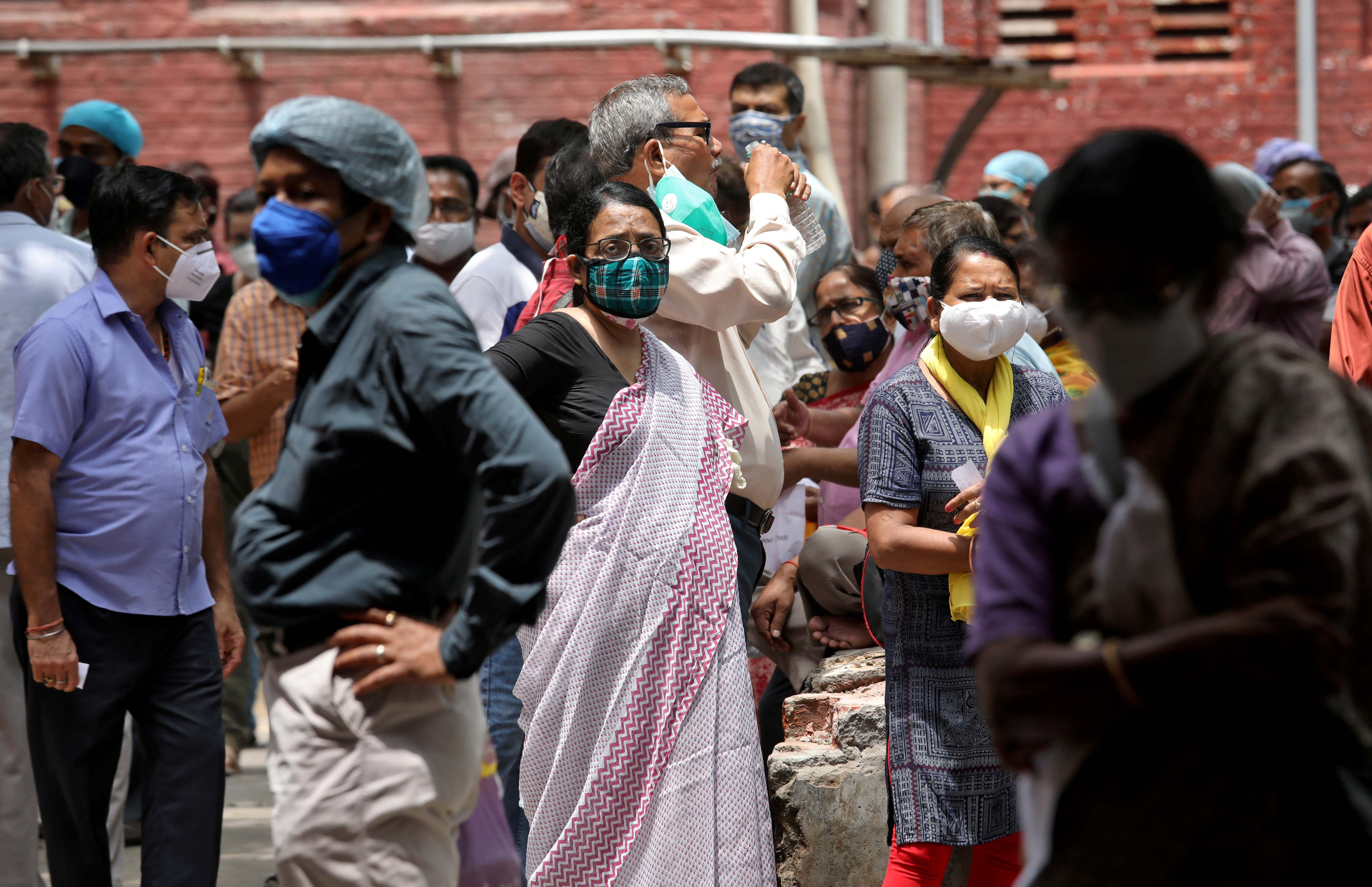 People wearing protective face masks wait to receive their second dose of COVISHIELD, a coronavirus disease (COVID-19) vaccine manufactured by Serum Institute of India, outside a vaccination centre in Kolkata, India, May 12, 2021. REUTERS/Rupak De Chowdhuri