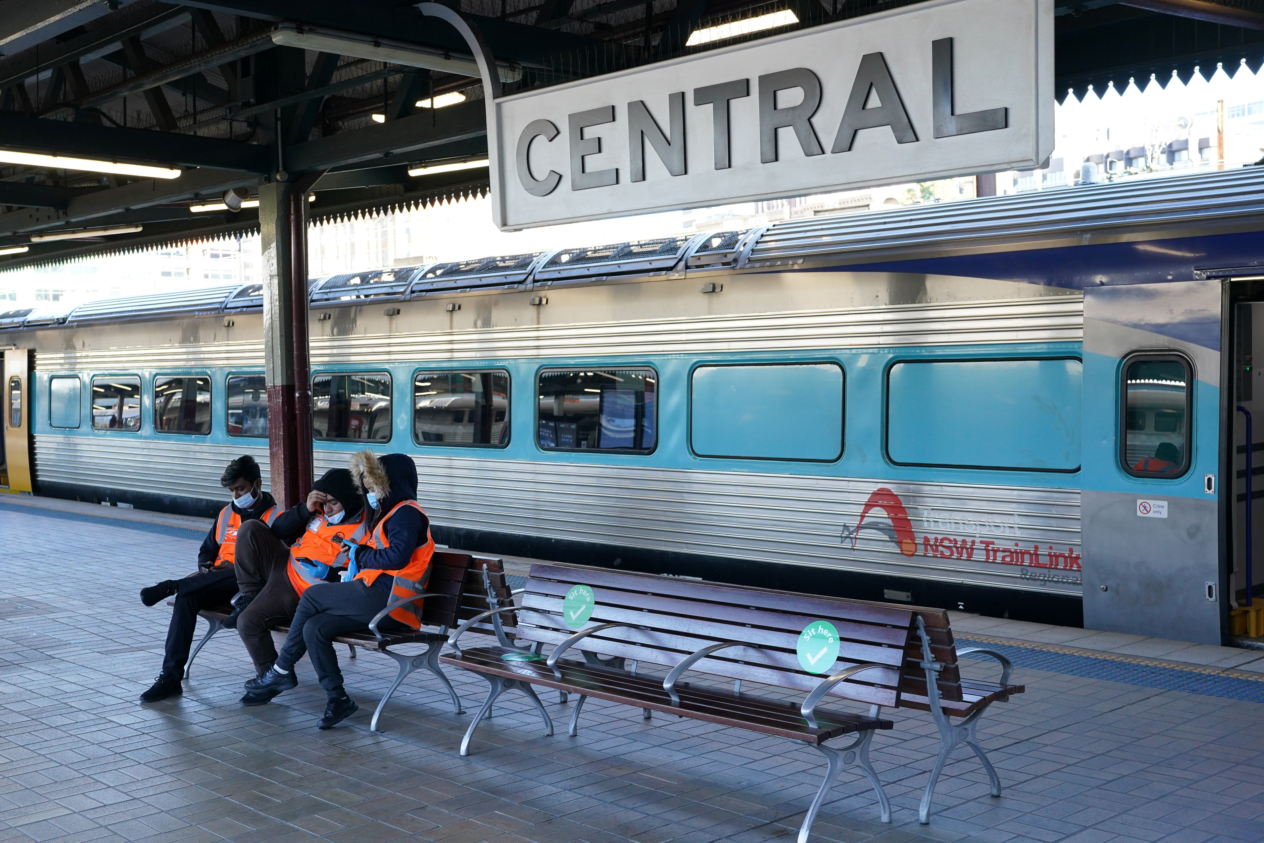Transport workers sit together on a train platform devoid of passengers at Central Station in the city centre as the City of Sydney and three adjacent local government areas begin a week-long lockdown to curb an outbreak of the coronavirus disease (COVID-19) in Sydney, Australia, June 26, 2021.  REUTERS/Loren Elliott