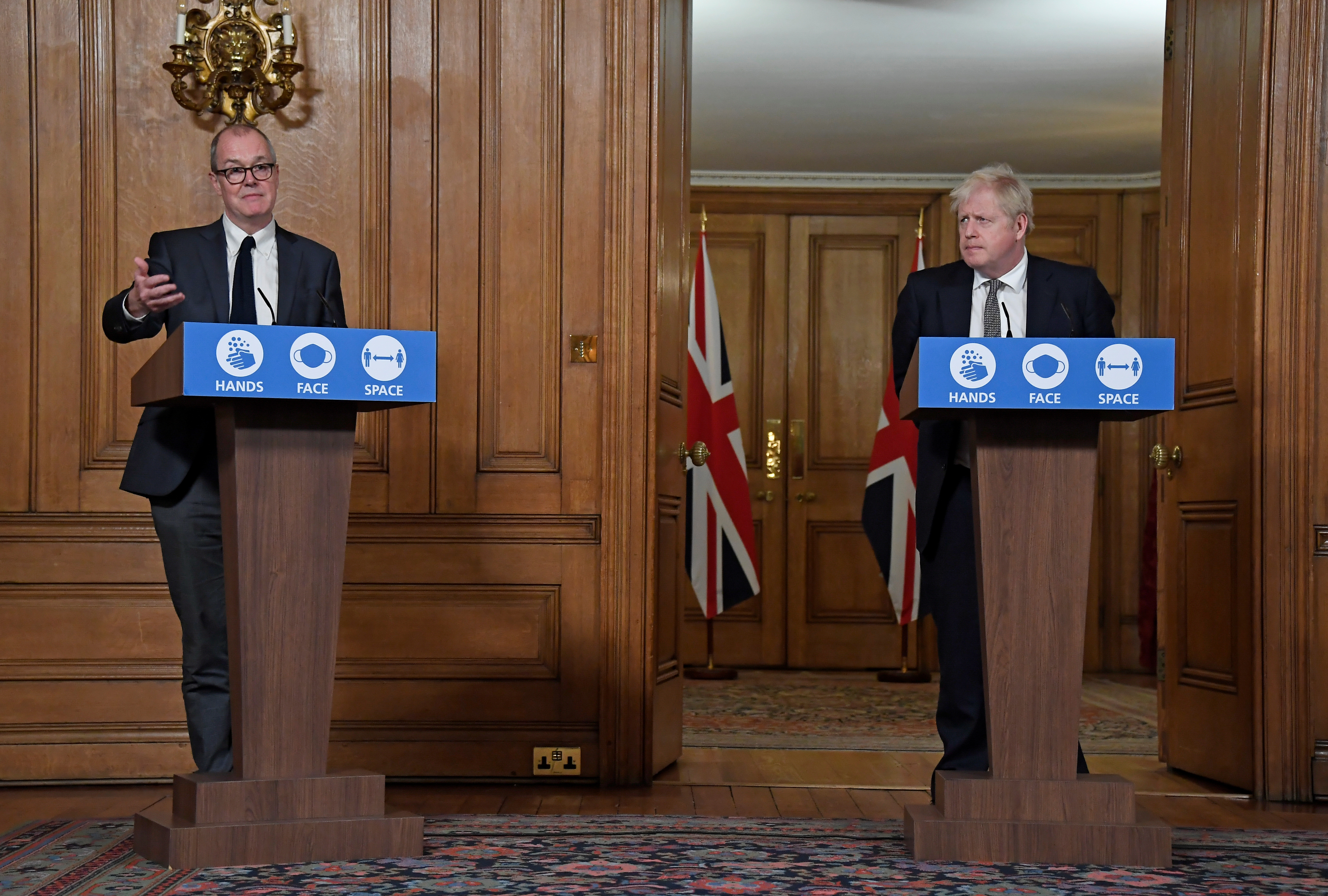 Britain's Prime Minister Boris Johnson watches Chief Scientific Adviser Sir Patrick Vallance speak during a press conference where he is expected to announce new restrictions to help combat the coronavirus disease (COVID-19) outbreak, at 10 Downing Street in London, Britain October 31, 2020. Alberto Pezzali/Pool via REUTERS