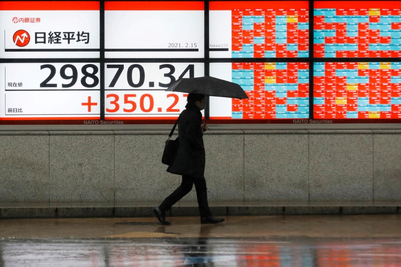 A man holding an umbrella walks in front of an electric board showing Nikkei index at a brokerage in Tokyo, Japan February 15, 2021. REUTERS/Kim Kyung-Hoon