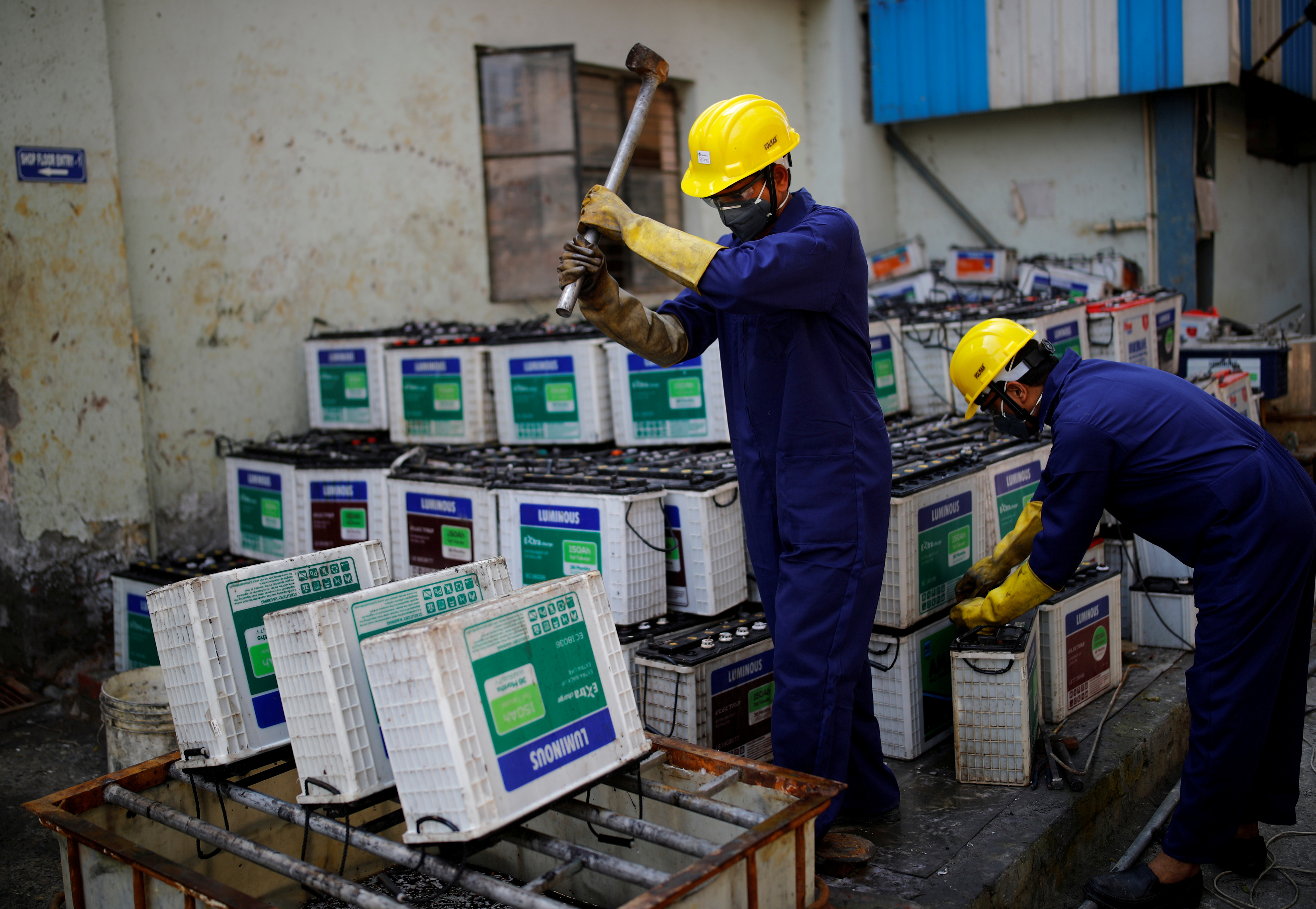 Workers dismantle batteries to obtain lead from them at ACE Green recycling Inc in Ghaziabad, on the outskirts of New Delhi, India, February 15, 2021. REUTERS/Adnan Abidi