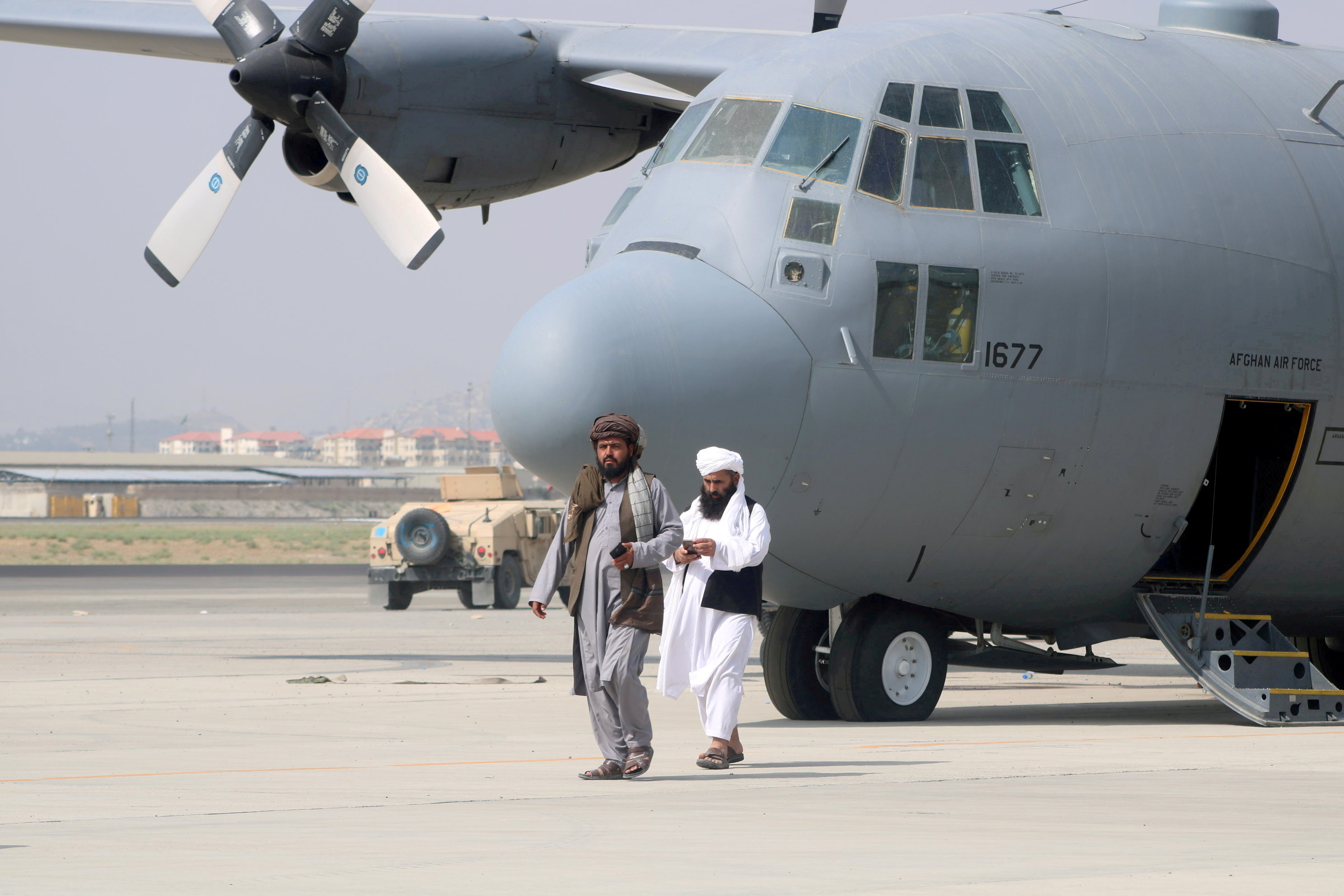 Taliban walk in front of a military airplane a day after the U.S. troops withdrawal from Hamid Karzai International Airport in Kabul, Afghanistan August 31, 2021. REUTERS/Stringer