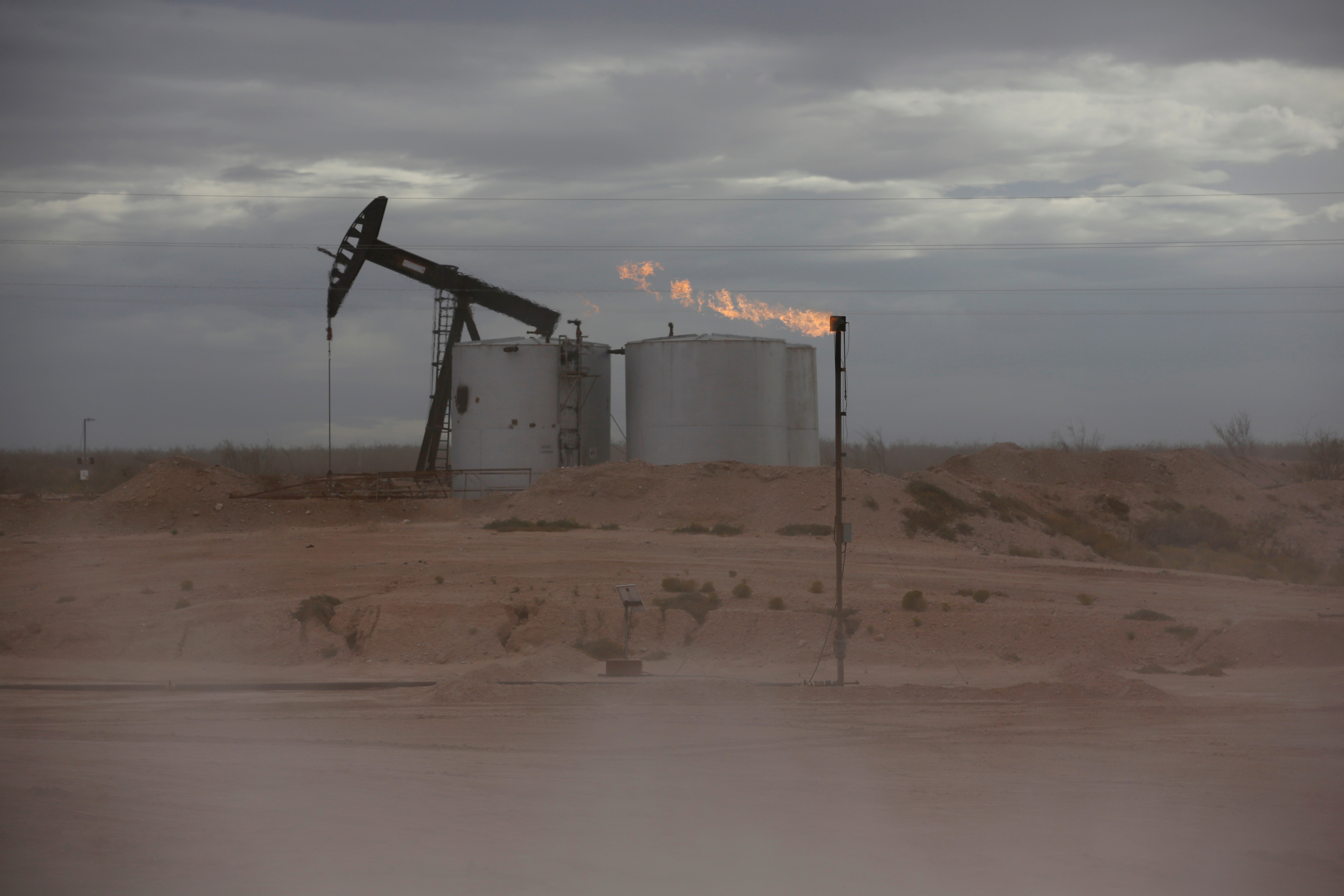 Dust blows around a crude oil pump jack and flare burning excess gas at a drill pad in the Permian Basin in Loving County, Texas, U.S. November 25, 2019. REUTERS/Angus Mordant/File Photo