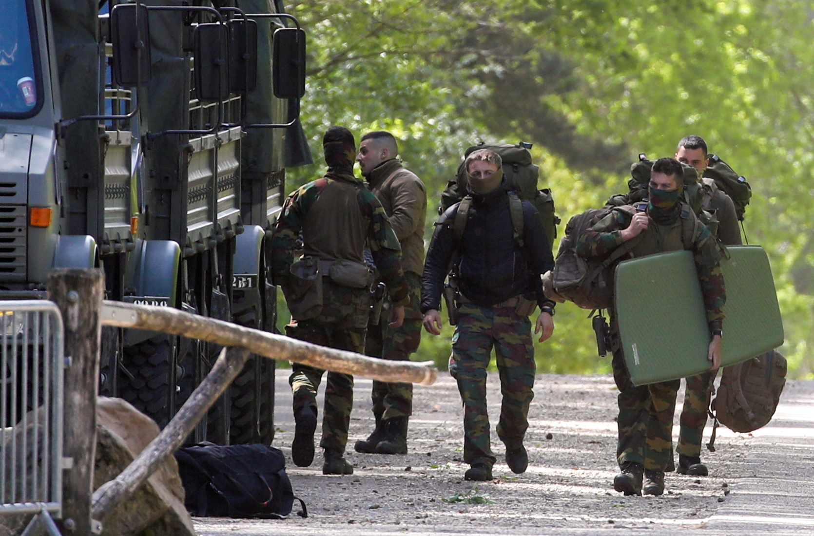 Belgian army members carry their bags at National Park Hoge Kempen while scouring to capture Belgian Jurgen Conings, a soldier who disappeared after threatening a virologist supportive of coronavirus disease (COVID-19) vaccines and coronavirus restrictions, in Maasmechelen, Belgium May 21, 2021. REUTERS/Yves Herman