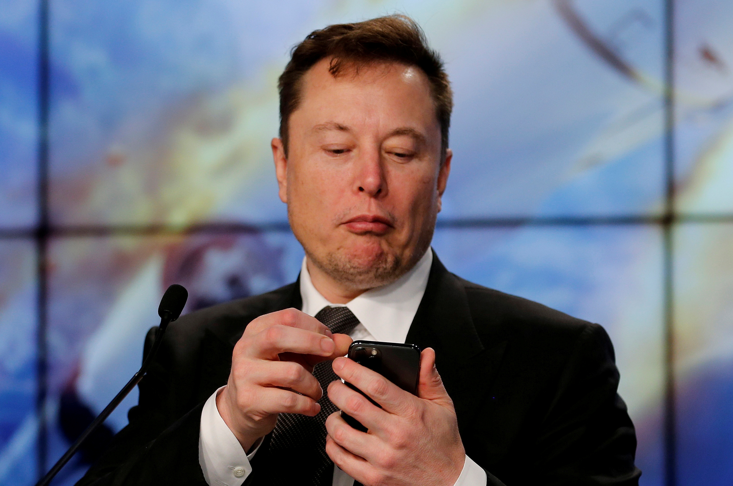 SpaceX founder and chief engineer Elon Musk looks at his mobile phone during a post-launch news conference to discuss the  SpaceX Crew Dragon astronaut capsule in-flight abort test at the Kennedy Space Center in Cape Canaveral, Florida, U.S. January 19, 2020. REUTERS/Joe Skipper/File Photo