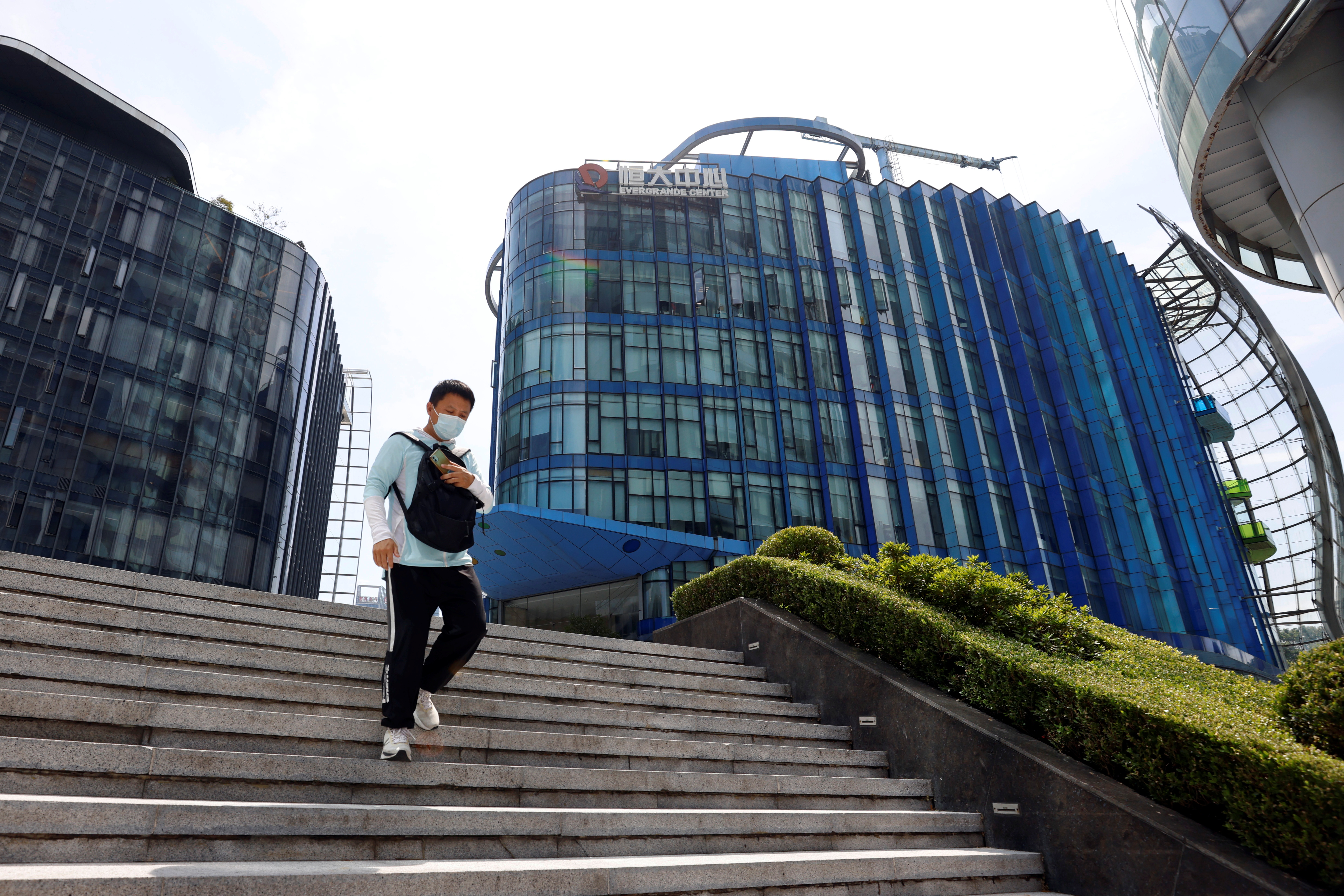 A man walks past the Evergrande Center of China Evergrande Group in Shanghai, China, September 24, 2021. REUTERS/Aly Song