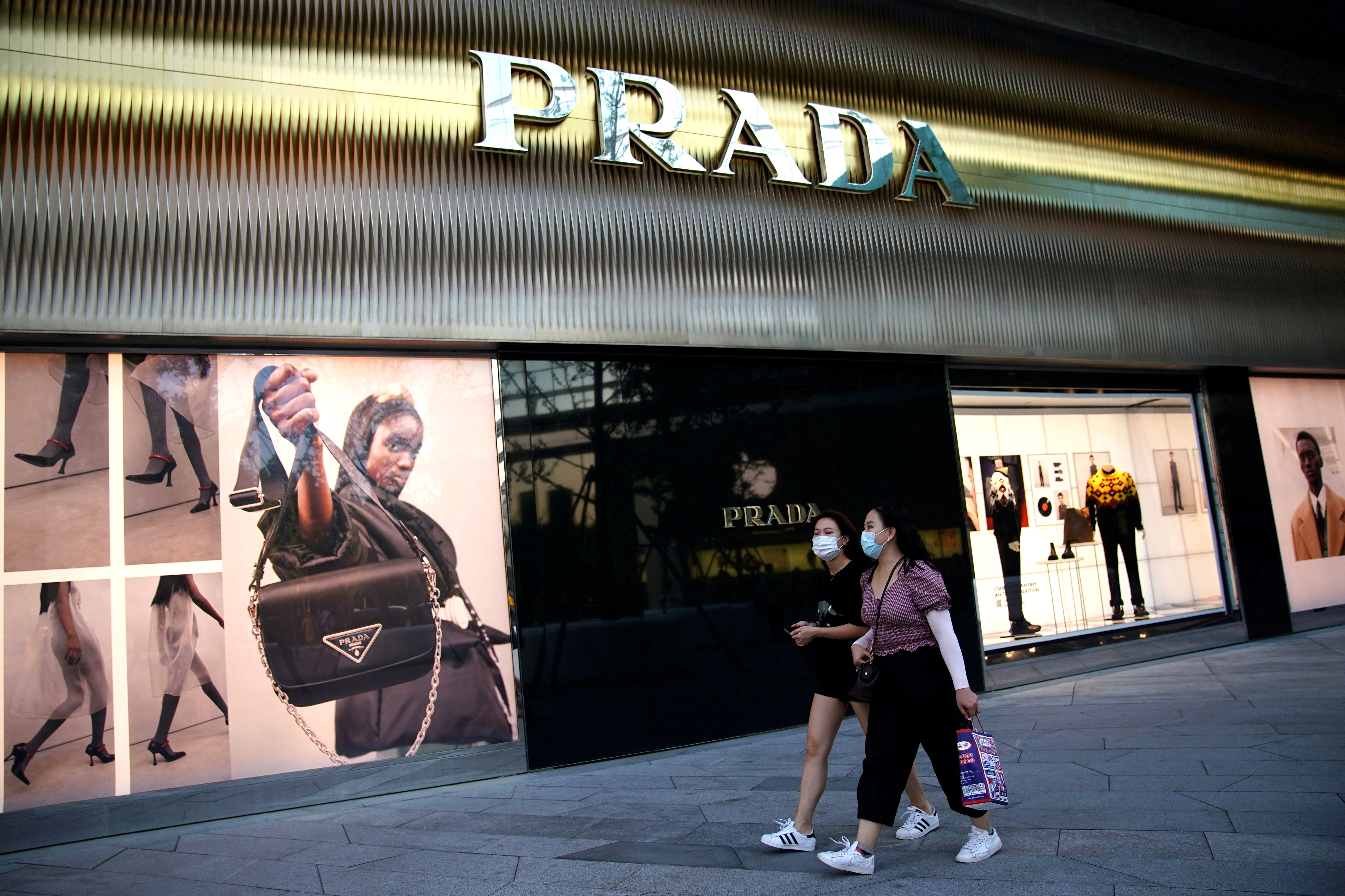 People wearing face masks walk past a store of Italian luxury brand Prada at a shopping complex in Beijing, China September 19, 2020.  REUTERS/Tingshu Wang