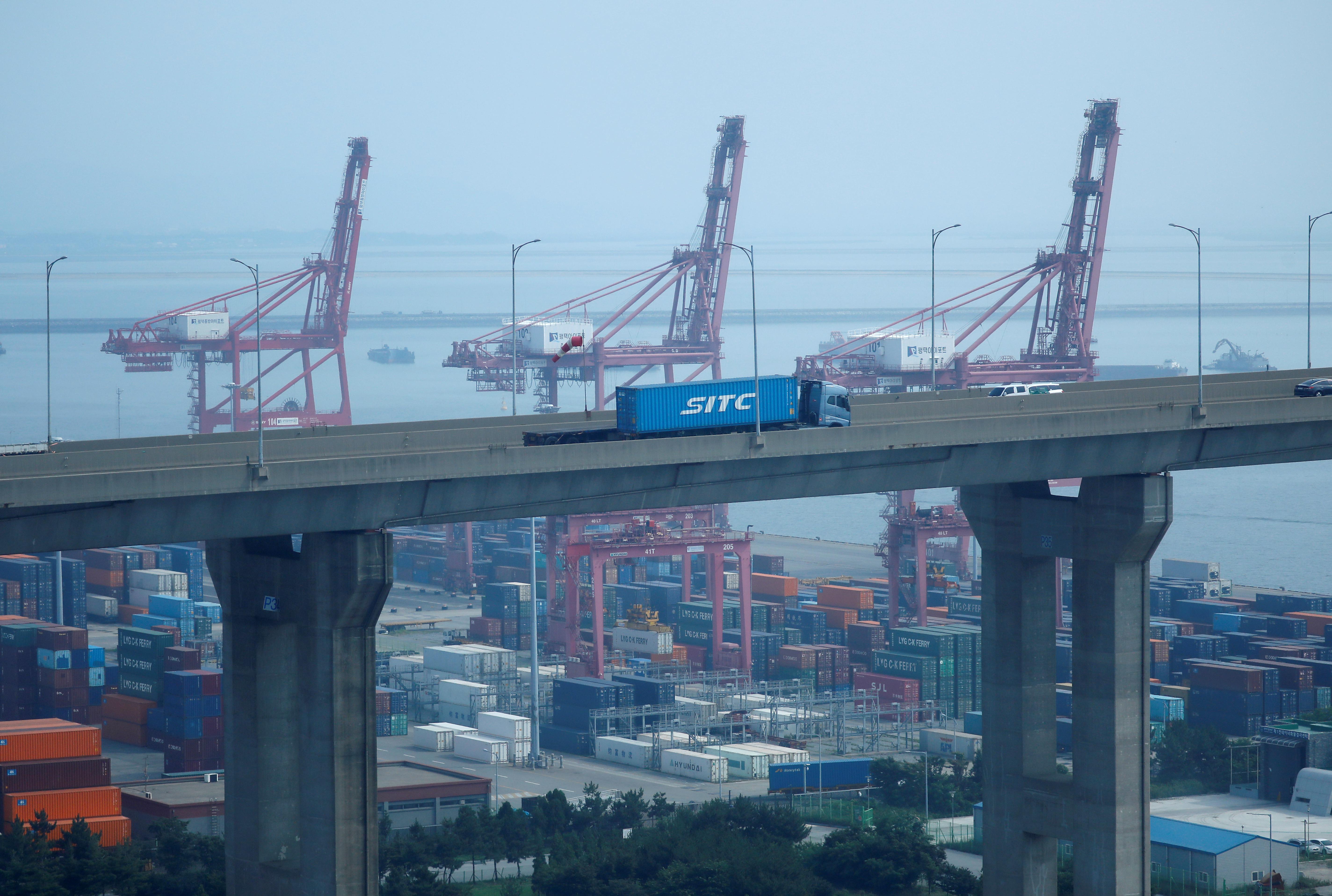 A truck carrying a shipping container travels past cranes at Pyeongtaek port in Pyeongtaek, South Korea, July 9, 2020.    REUTERS/Kim Hong-Ji
