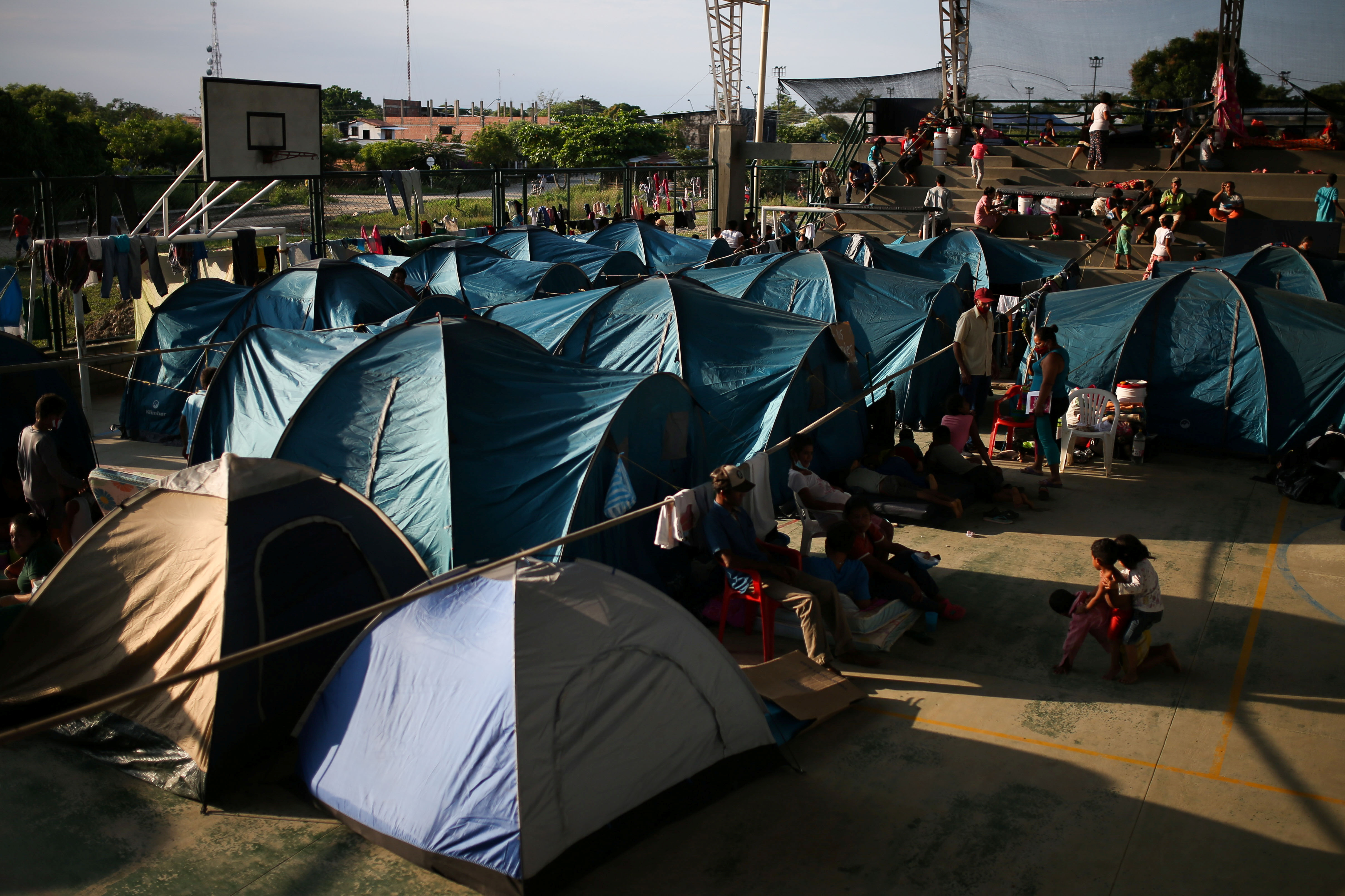 Venezuelan migrants are seen inside a coliseum where a temporary camp has been set up, after fleeing their country due to military operations, according to the Colombian migration agency, in Arauquita, Colombia March 27, 2021. REUTERS/Luisa Gonzalez