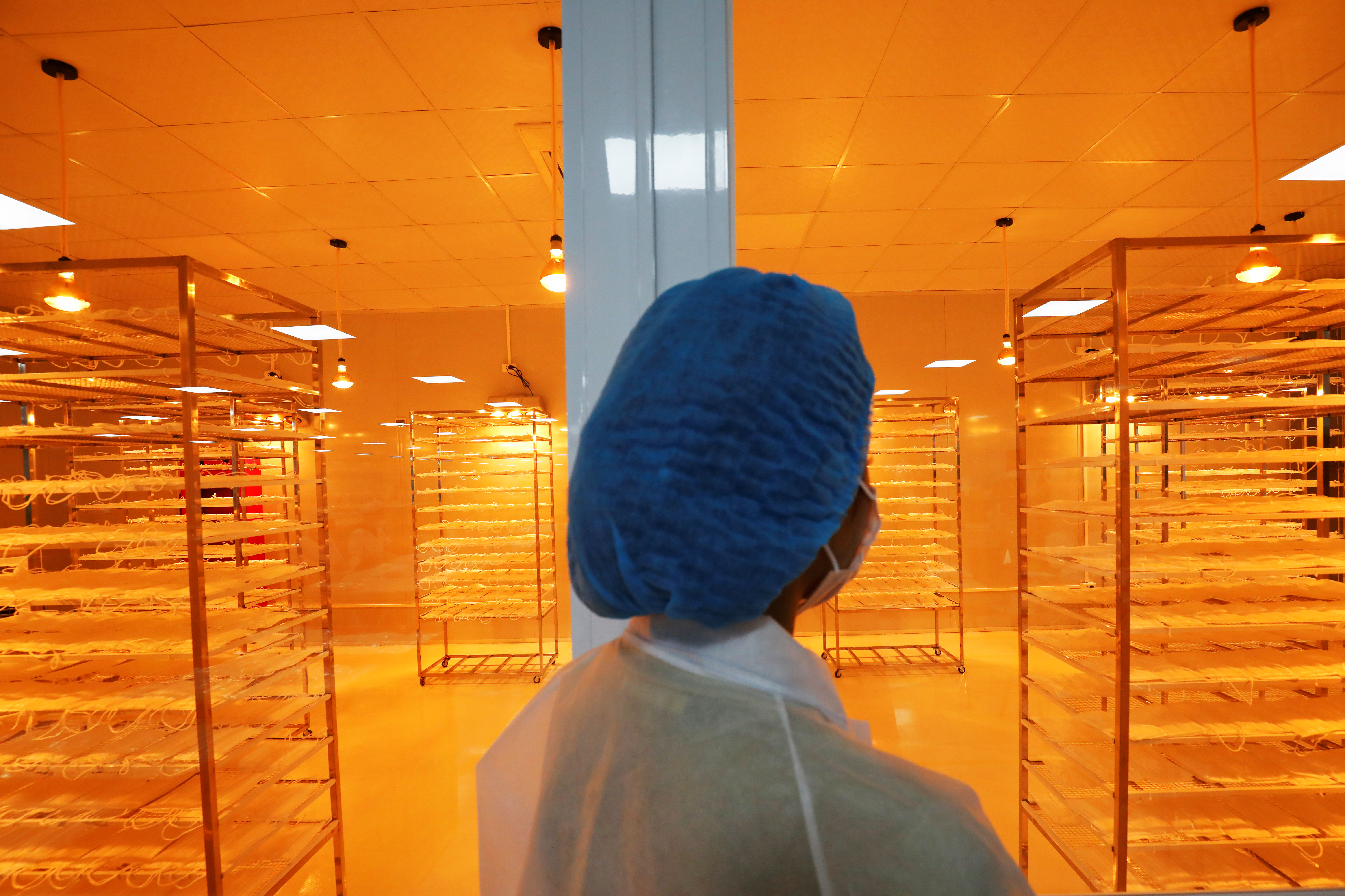 A woman checks medical protective masks under infrared light at An Phu company's production facility for domestic and international markets, amid of the spread of the coronavirus disease (COVID-19), in Bac Ninh province, Vietnam August 5, 2020. REUTERS/Kham