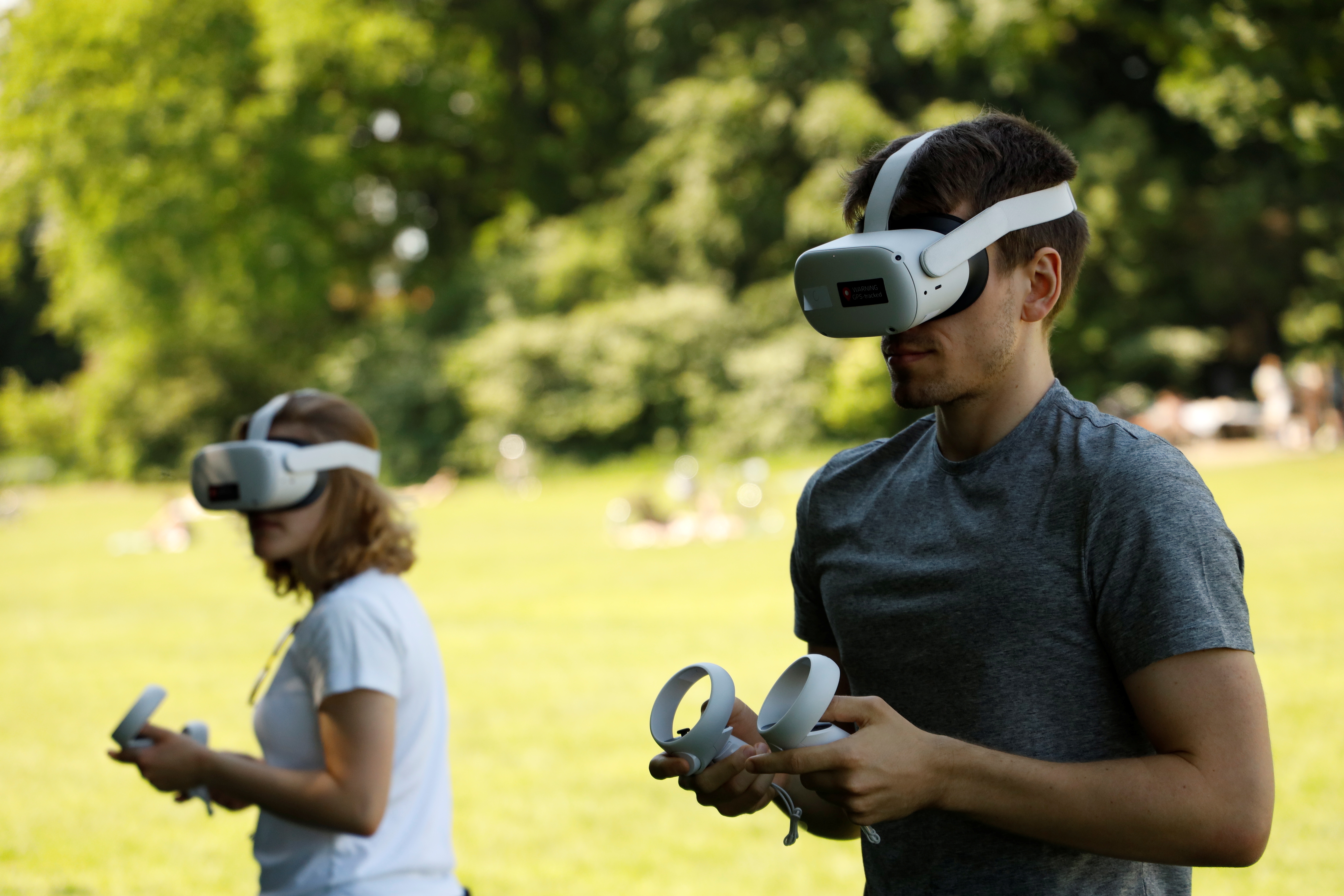 Participants Adam and Rebecca take part in an experiment, where researchers try to use virtual reality goggles to teach people about how virus infections spread, conducted in a park, amid the coronavirus disease (COVID-19) pandemic, in Copenhagen, Denmark, June 6, 2021. Picture taken June 6, 2021. REUTERS/Tim Barsoe