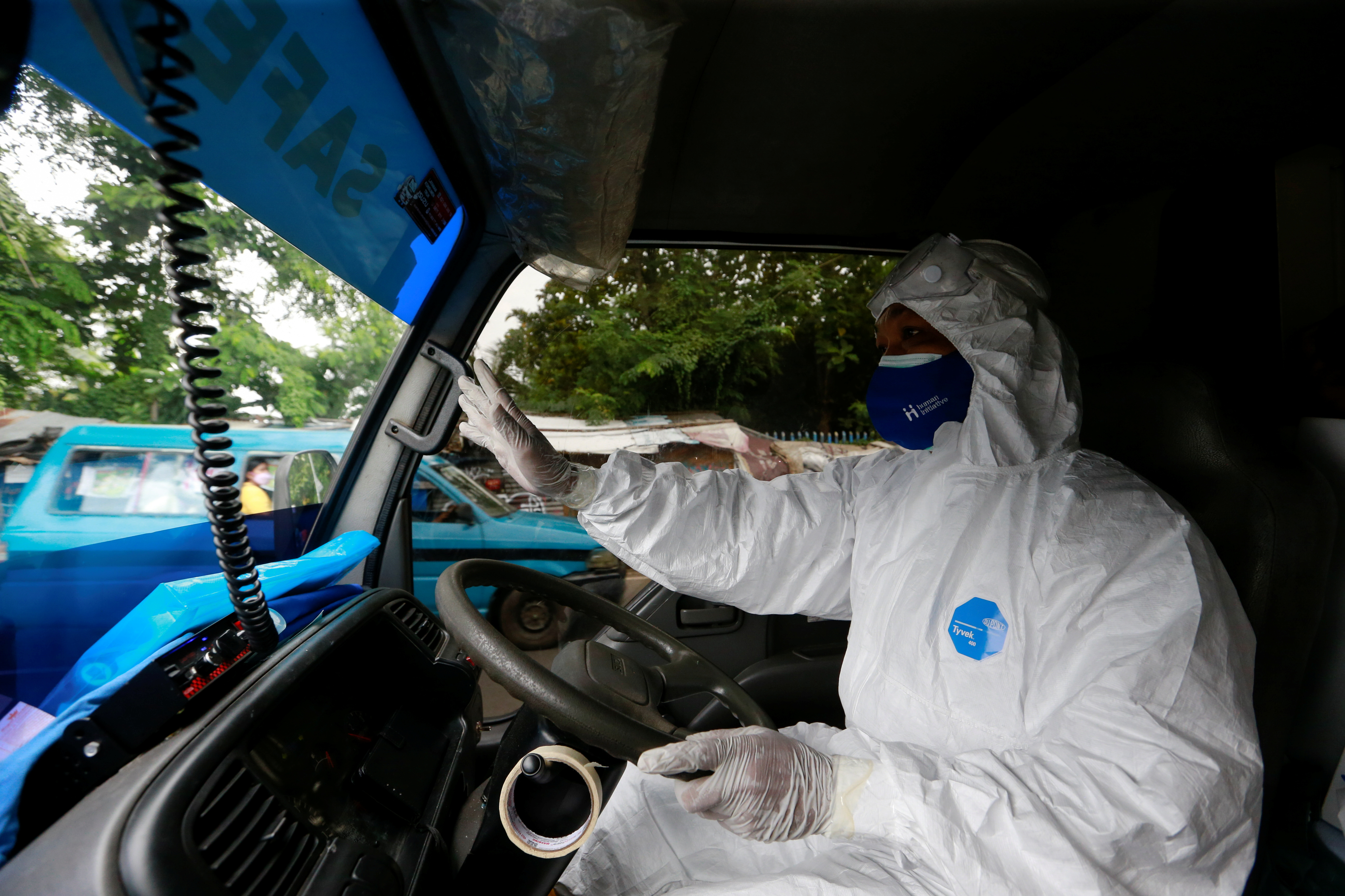 Sunaryo, 53, drives an ambulance as he delivers a patient suffering from coronavirus disease (COVID-19), as cases surge in Depok, on the outskirts of Jakarta, Indonesia, July 13, 2021. REUTERS/Ajeng Dinar Ulfiana