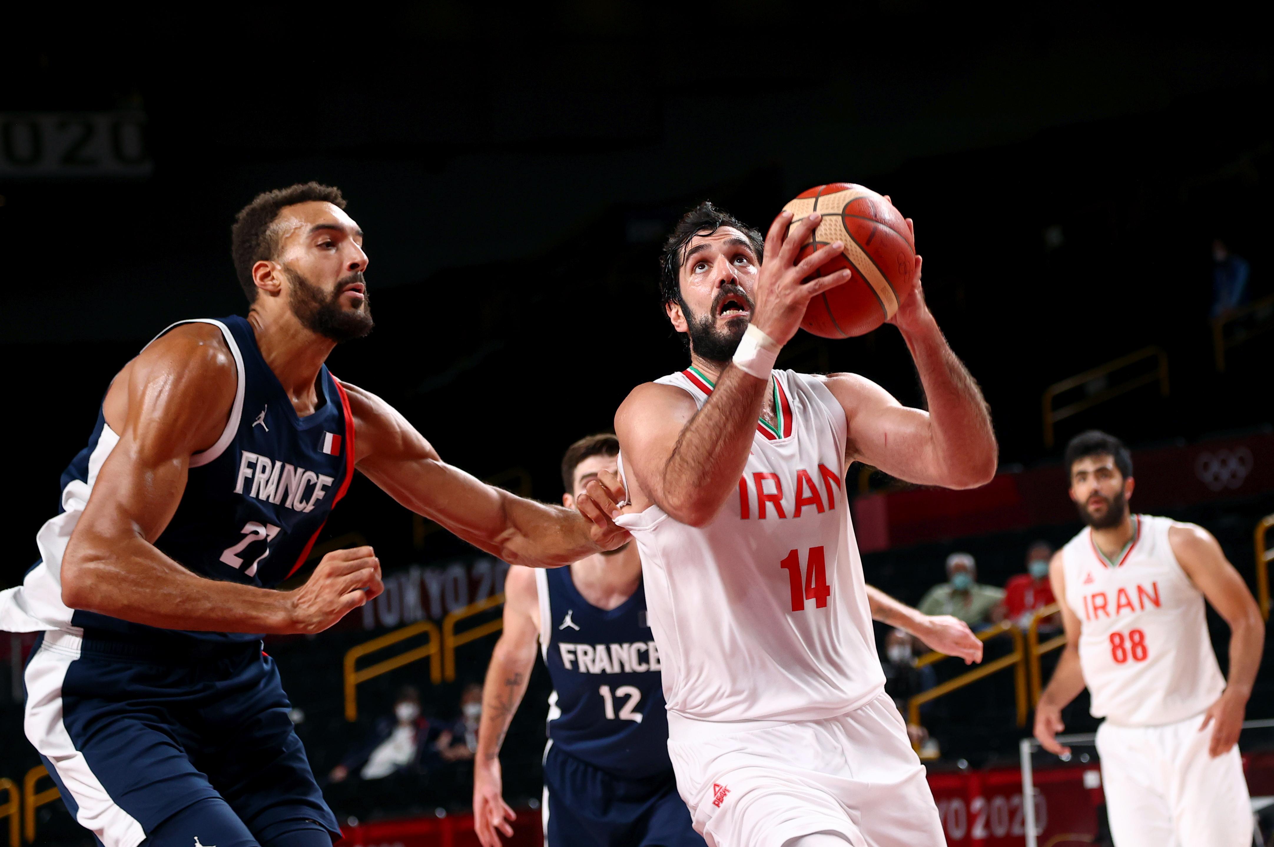 Tokyo 2020 Olympics - Basketball - Men - Group A - Iran v France - Saitama Super Arena, Saitama, Japan - July 31, 2021. Samad Nikkhah Bahrami of Iran in action with Rudy Gobert of France REUTERS/Brian Snyder