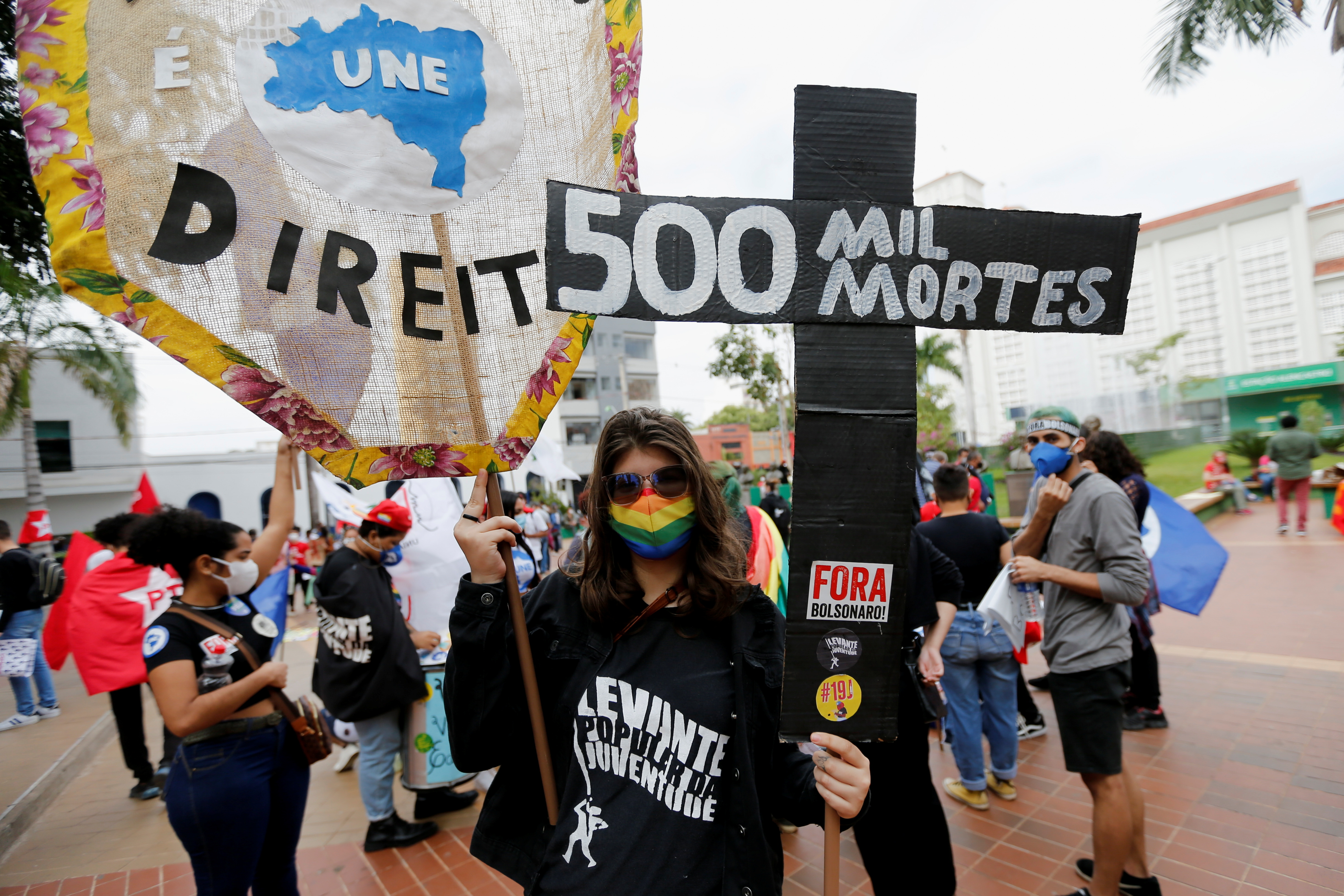 """A person holds a cross reading """"500.000 deaths"""" as people participate in a protest against Brazil's President Jair Bolsonaro and his handling of the coronavirus disease (COVID-19) pandemic in Cuiaba, Brazil, June 19, 2021. REUTERS/Mariana Greif"""