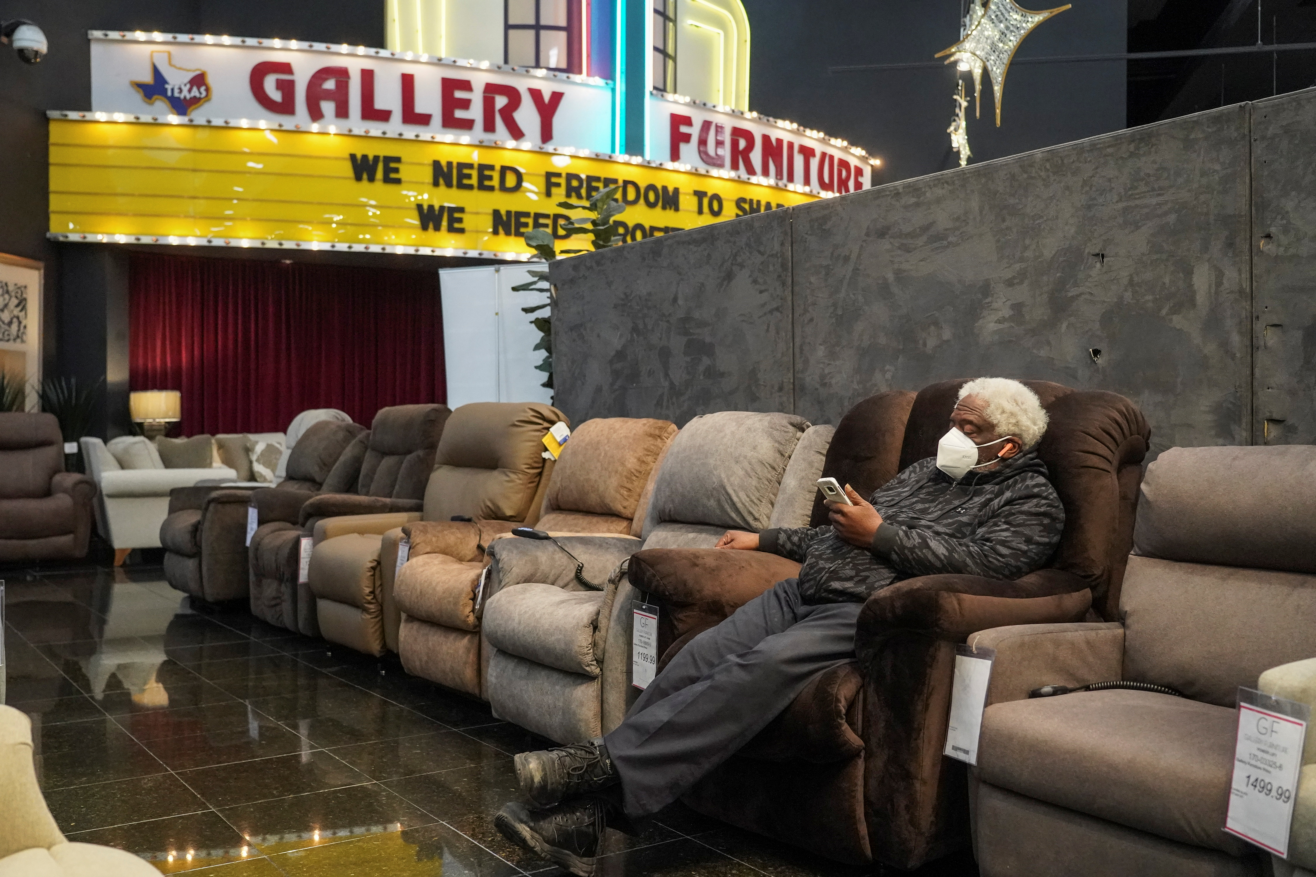 Alvin Williams, 66, checks on his smartphone while taking a shelter at Gallery Furniture store which opened its door and transformed into a warming station after winter weather caused electricity blackouts in Houston, Texas, U.S. February 17, 2021.  REUTERS/Go Nakamura