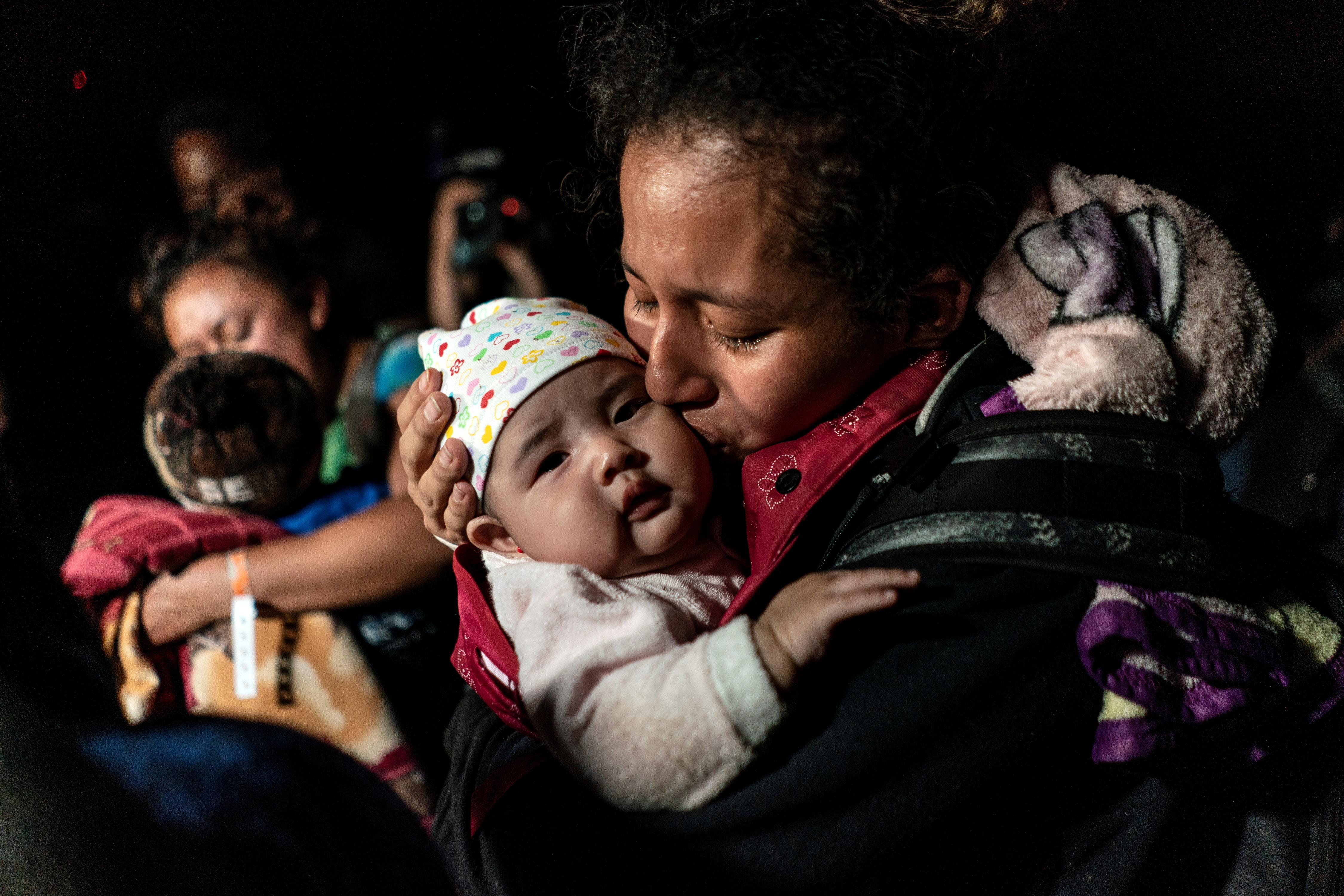 Ceidy, an asylum-seeking migrant mother from Guatemala, kisses her 3-month-old baby Bridget while waiting to be escorted by the U.S. Border Patrol agents after crossing the Rio Grande river into the United States from Mexico in Roma, Texas, U.S. April 7, 2021. Picture taken April 7, 2021. REUTERS/Go Nakamura/File Photo