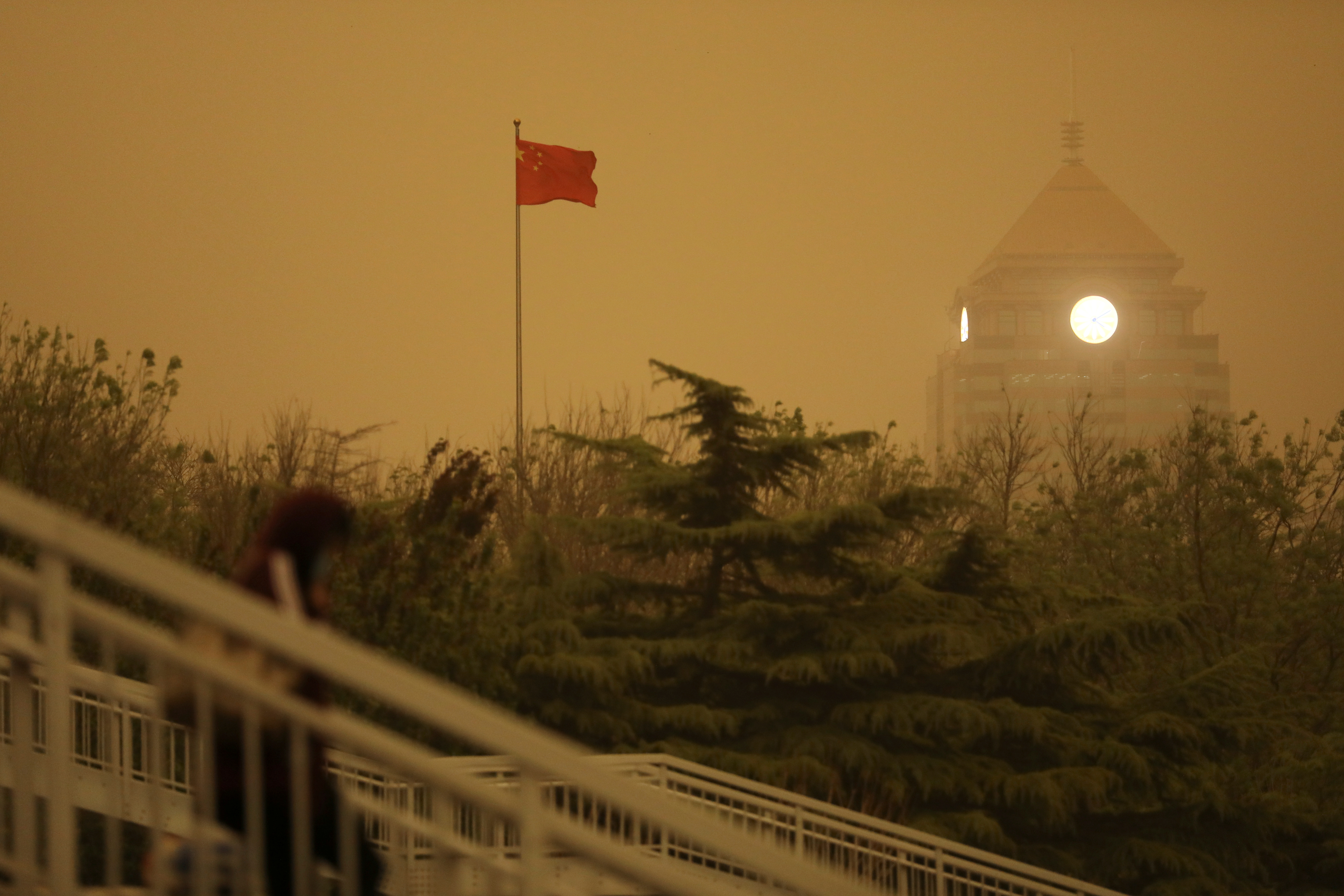 A pedestrian walks near a Chinese flag amid a duststorm in Beijing, China April 15, 2021. REUTERS/Tingshu Wang