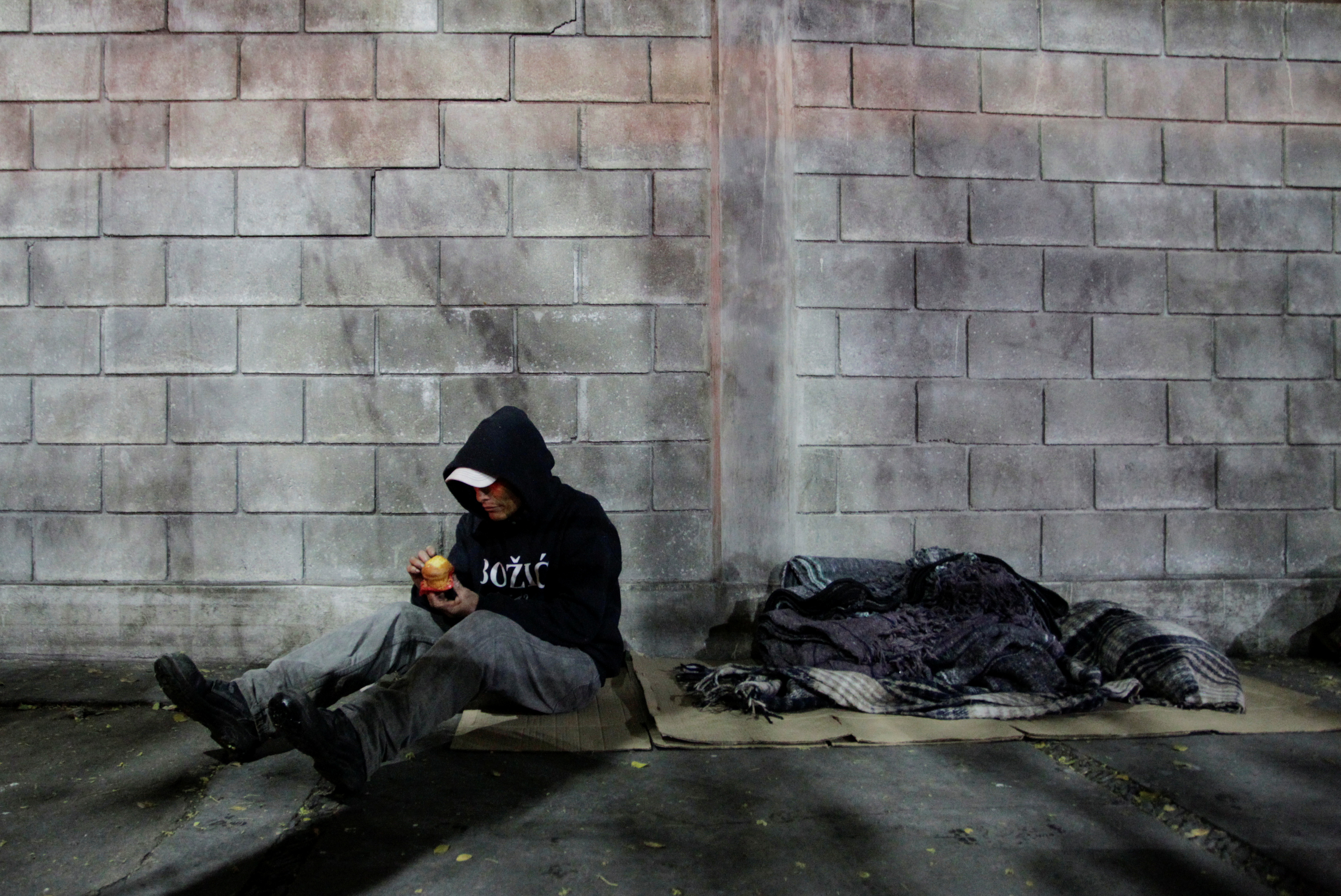 A man eats a piece of bread as he prepares to sleep on the street during a cold front in Monterrey, Mexico February 15, 2021. REUTERS/Daniel Becerril
