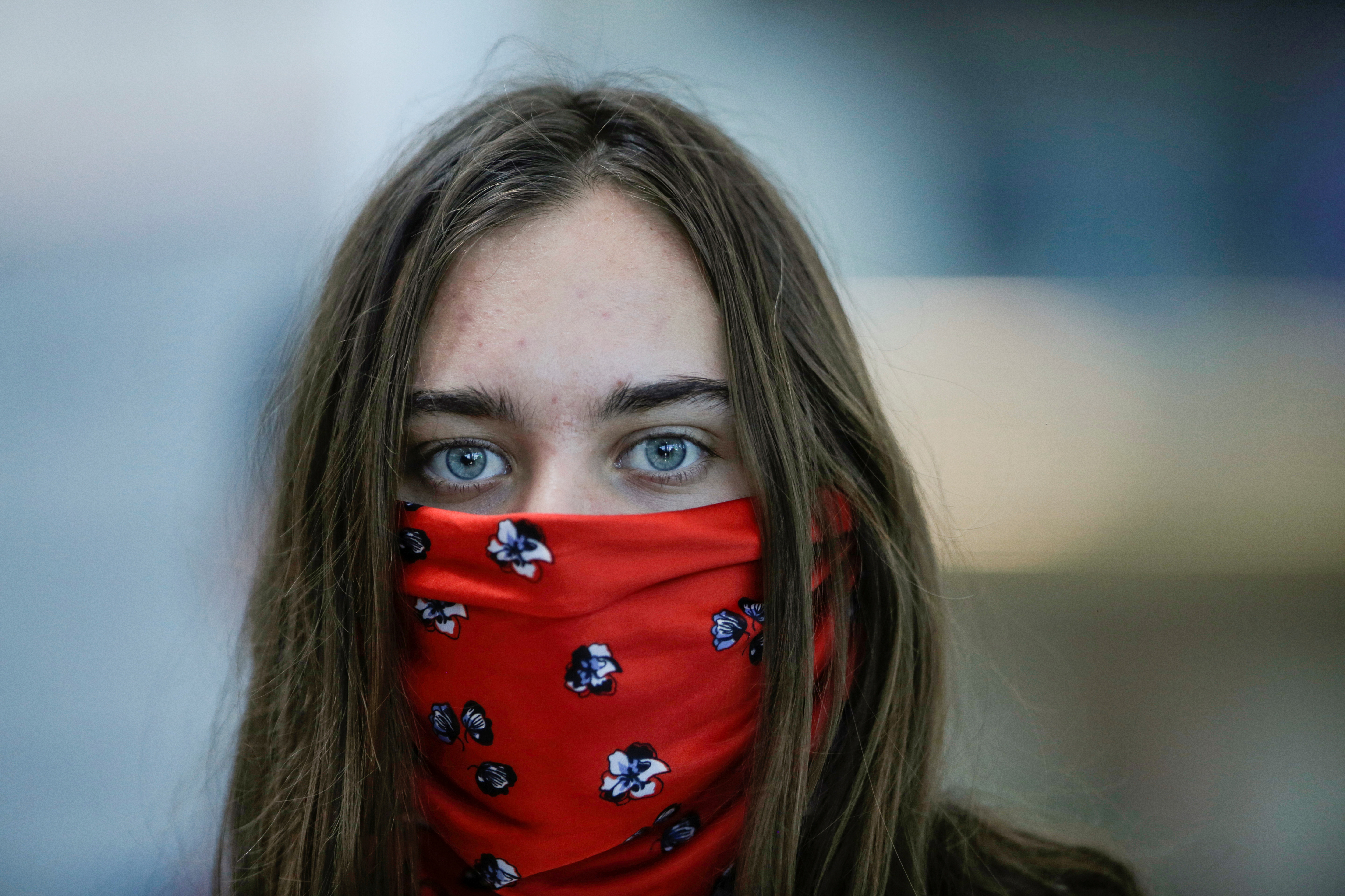 A tourist with covered face waits to check in for her flight at Juan Santamaria International Airport , as Costa Rica tourism industry braces for coronavirus disease (COVID-19) outbreak, in Alajuela, Costa Rica March 19, 2020. REUTERS/Juan Carlos Ulate/File Photo
