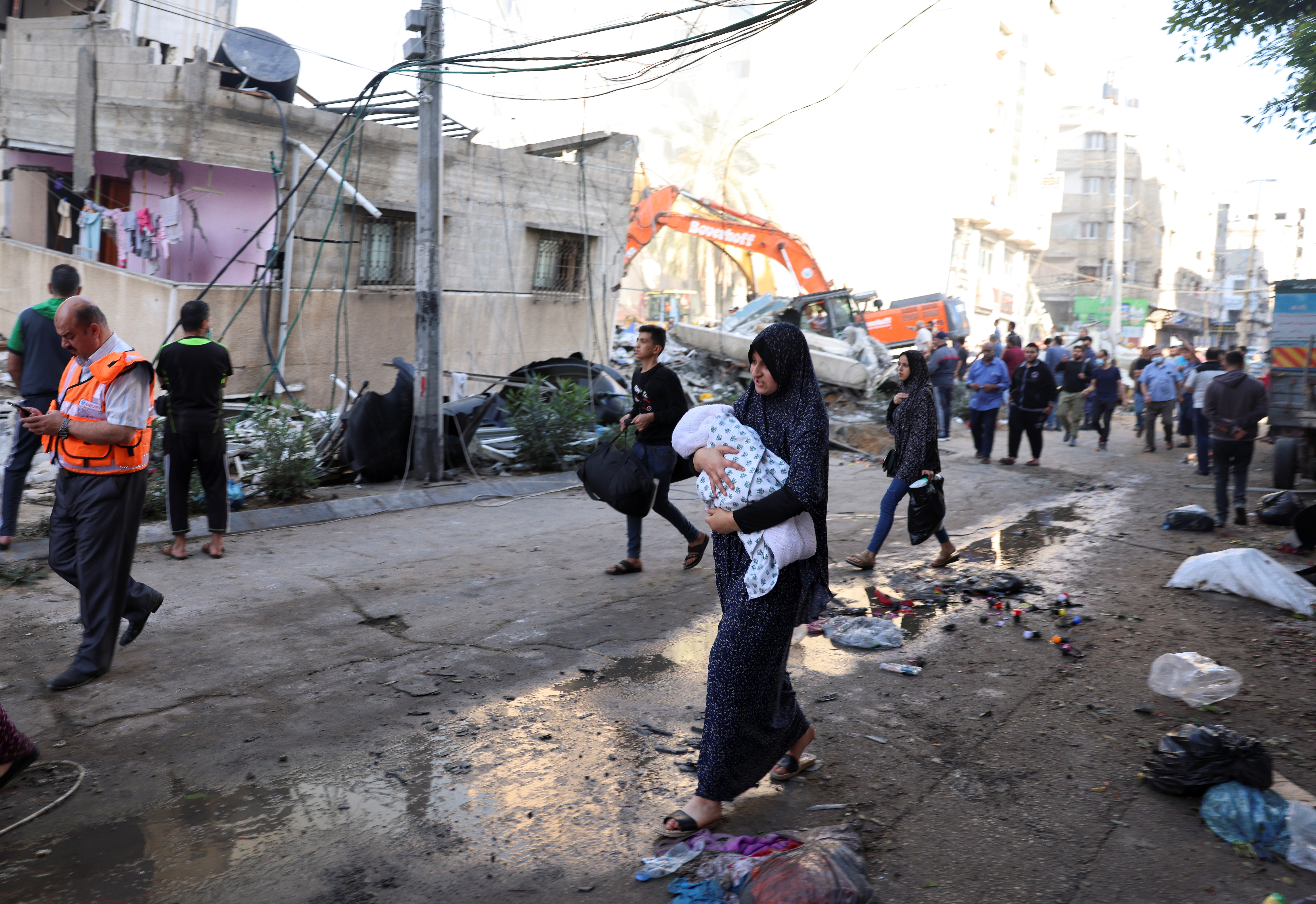 People walk past debris in a street at the site of Israeli air strikes, in Gaza City May 16, 2021. REUTERS/Mohammed Salem
