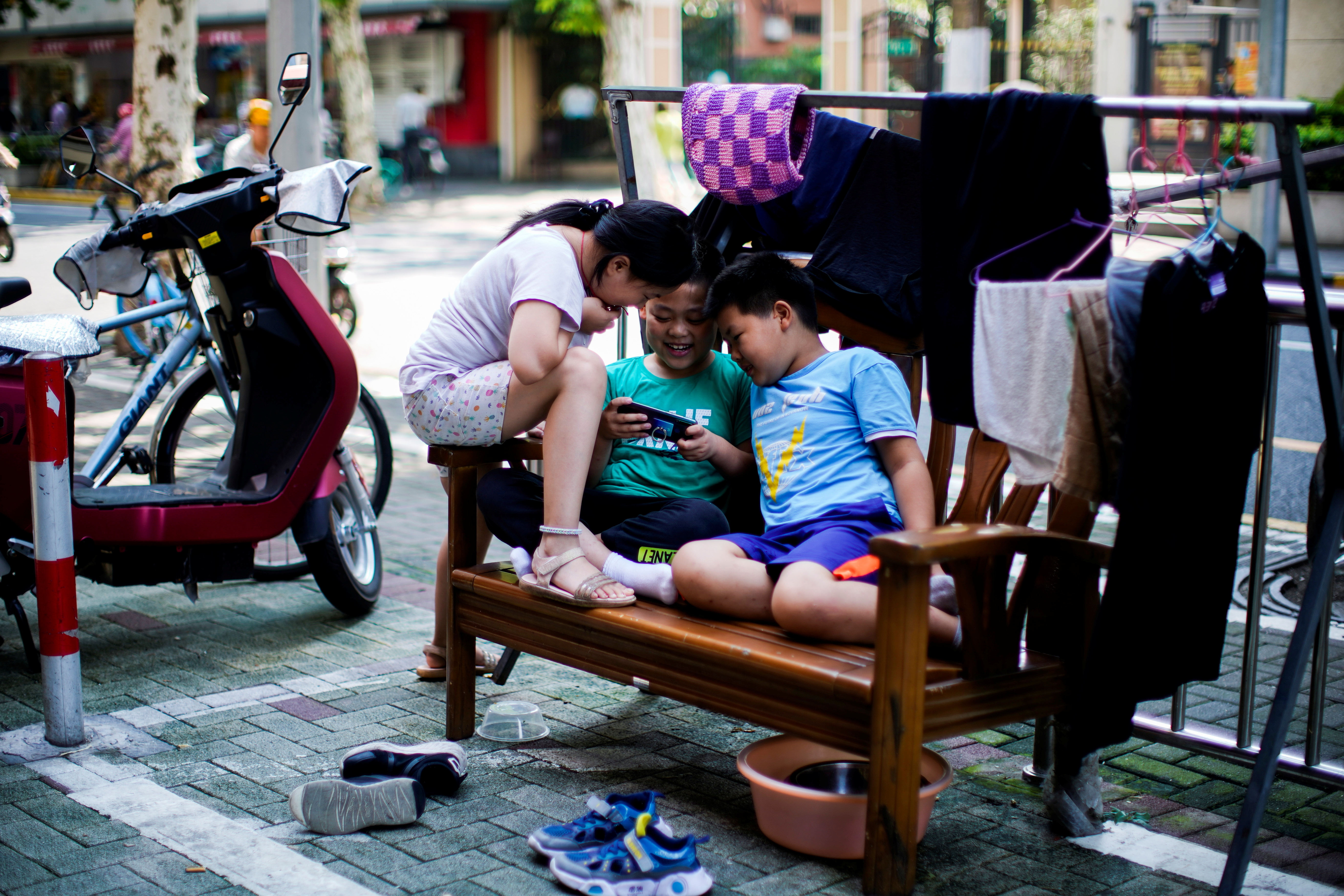 Children look at a phone on a street in Shanghai, China August 28, 2021. REUTERS/Aly Song