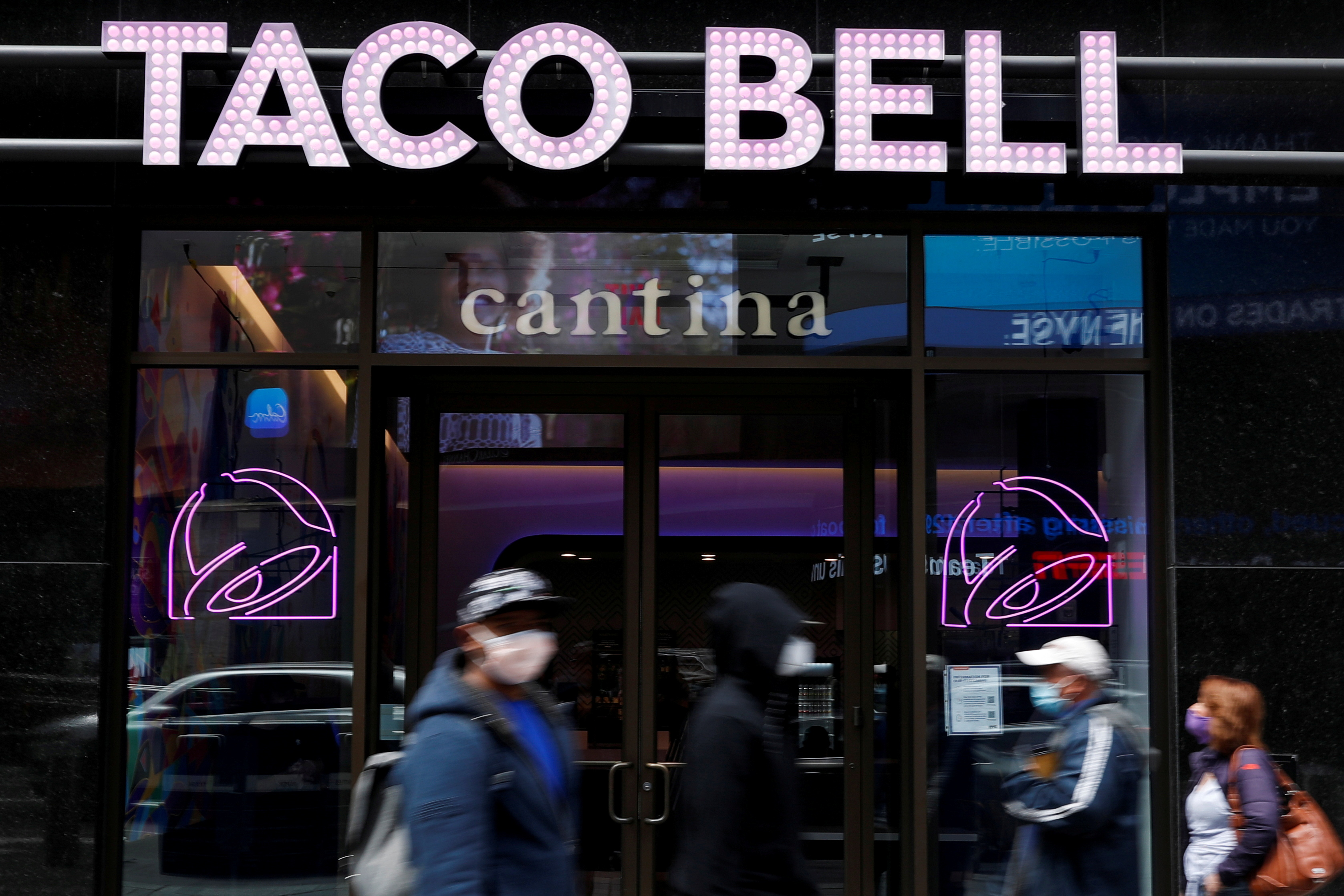 People walk by Taco Bell's first digital-only U.S. cantina location at Times Square in New York City, U.S., April 14, 2021. REUTERS/Shannon Stapleton/File Photo