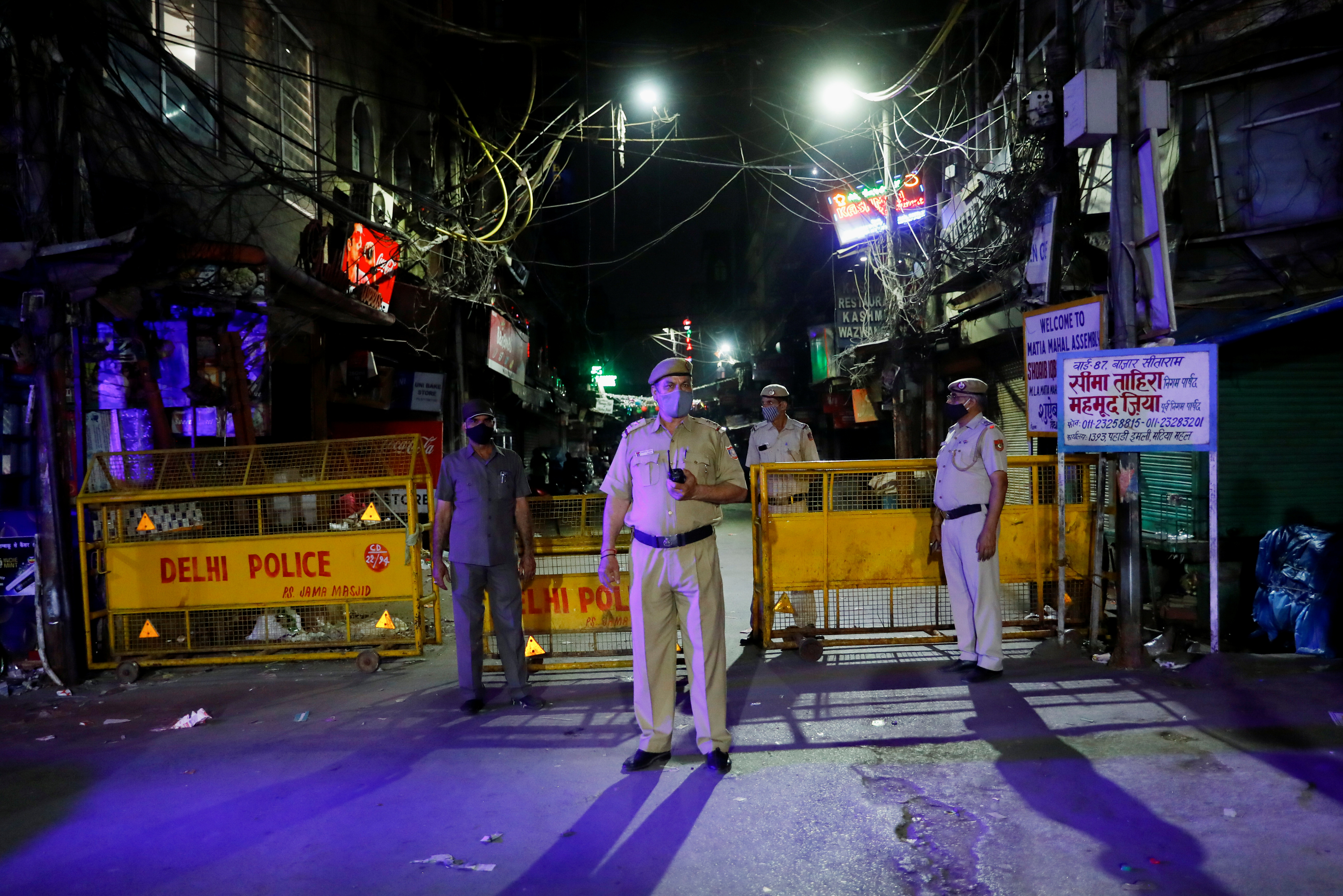 Police officers stand guard on a deserted street during a curfew to limit the spread of the coronavirus disease (COVID-19), in New Delhi, April 6, 2021. REUTERS/Adnan Abidi