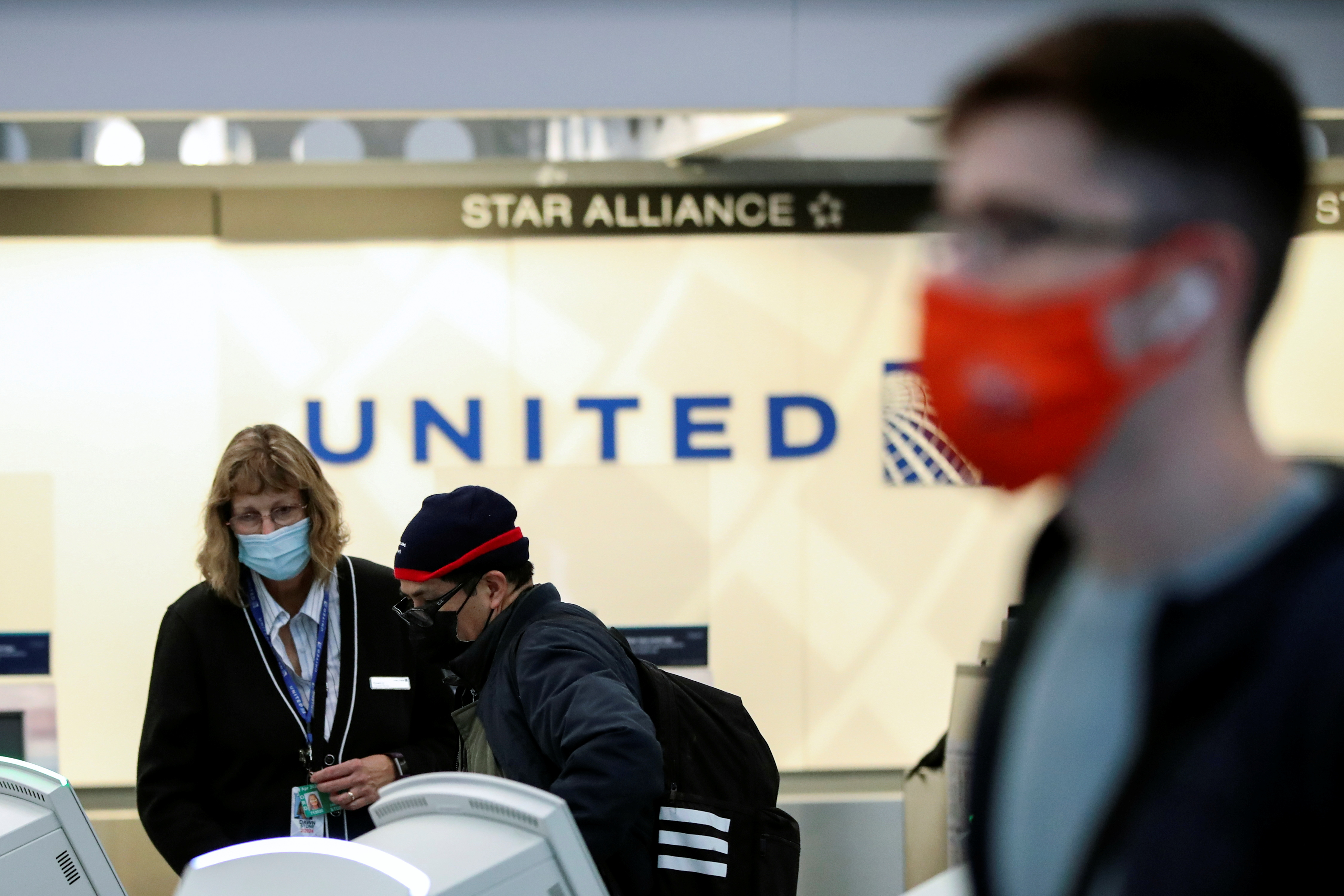 United Airlines agent helps a customer check-in for his flight at O'Hare International Airport ahead of the Thanksgiving holiday during the coronavirus disease (COVID-19) pandemic, in Chicago, Illinois, U.S. November 25, 2020. REUTERS/Kamil Krzaczynski