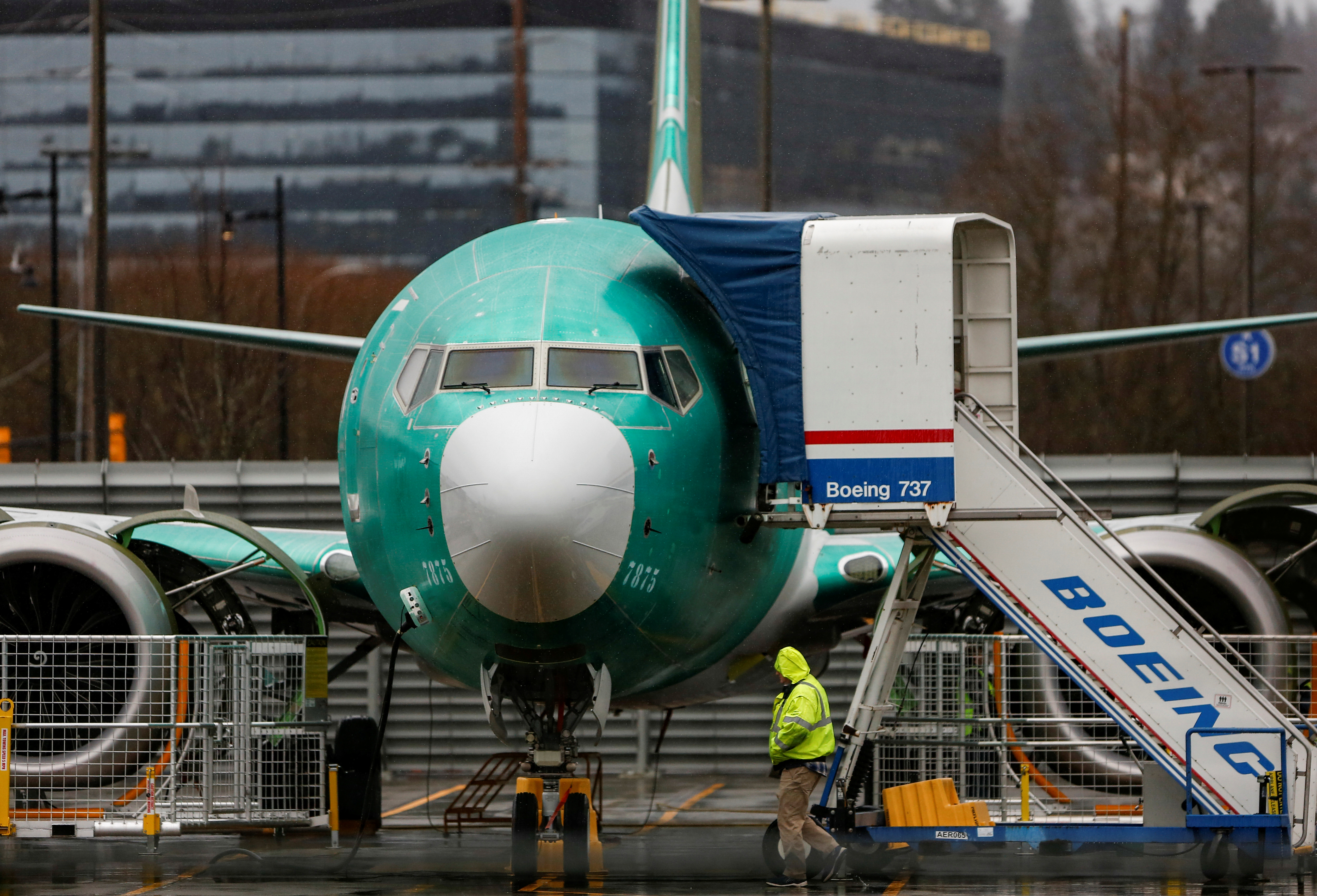 An employee walks past a Boeing 737 Max aircraft seen parked at the Renton Municipal Airport in Renton, Washington, U.S. January 10, 2020. REUTERS/Lindsey Wasson/Files