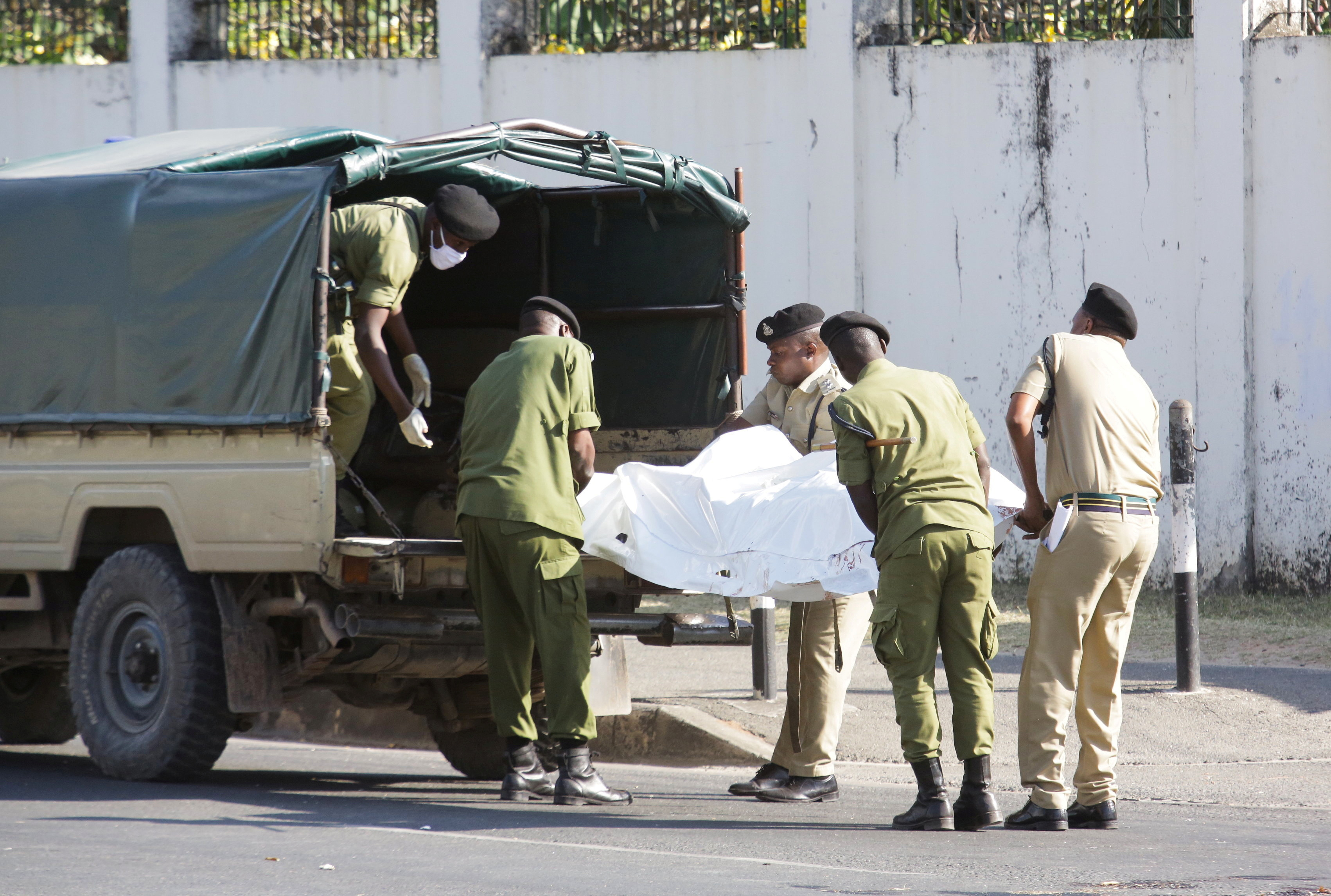 Tanzanian security forces remove the slain body of an attacker who was wielding an assault rifle, outside the French embassy in the Salenda area of Dar es Salaam, Tanzania August 25, 2021. REUTERS/Emmanuel Herman