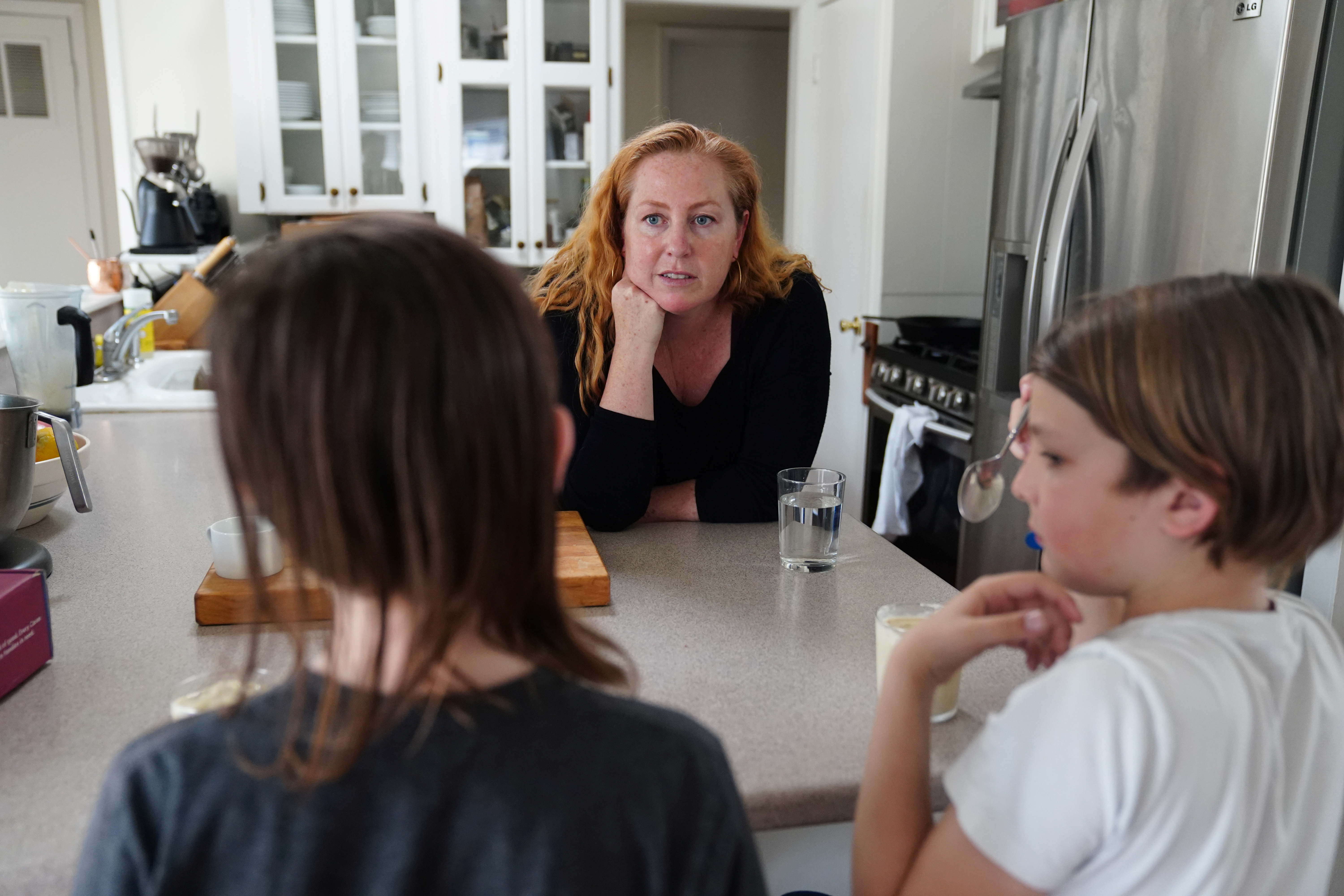 Kate Sullivan Morgan, who relocated with her family from San Francisco so her children could attend school in-person, gets her children an after school snack in Austin, Texas, U.S., March 12, 2021. Picture taken March 12, 2021.  REUTERS/Ilana Panich-Linsman