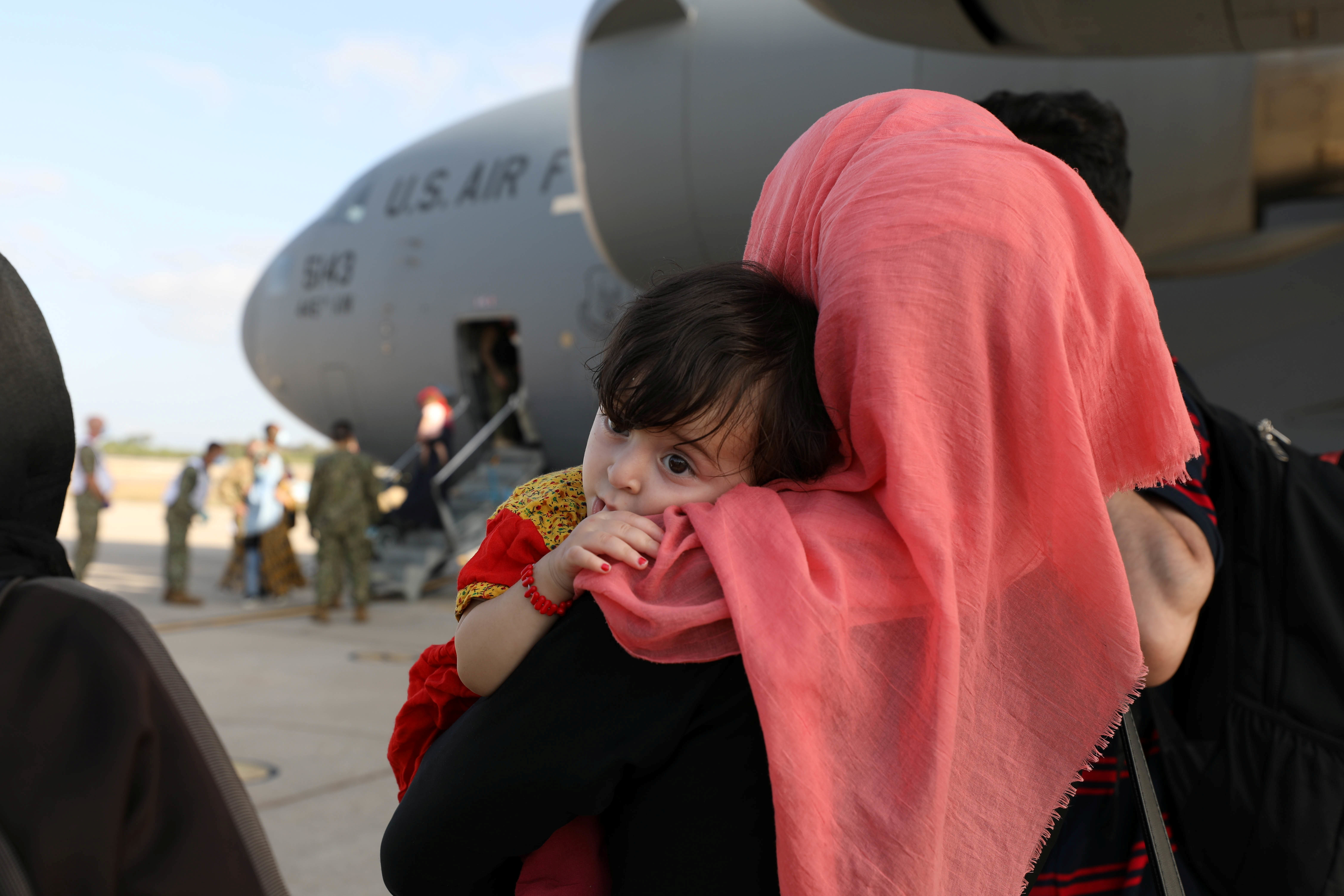 Evacuees from Afghanistan watch others disembark the aircraft after arriving at Naval Station (NAVSTA) Rota, Spain August 27, 2021. Picture taken August 27, 2021.  U.S. Navy/Mass Communication Specialist 2nd Class Katie Cox/Handout via REUTERS
