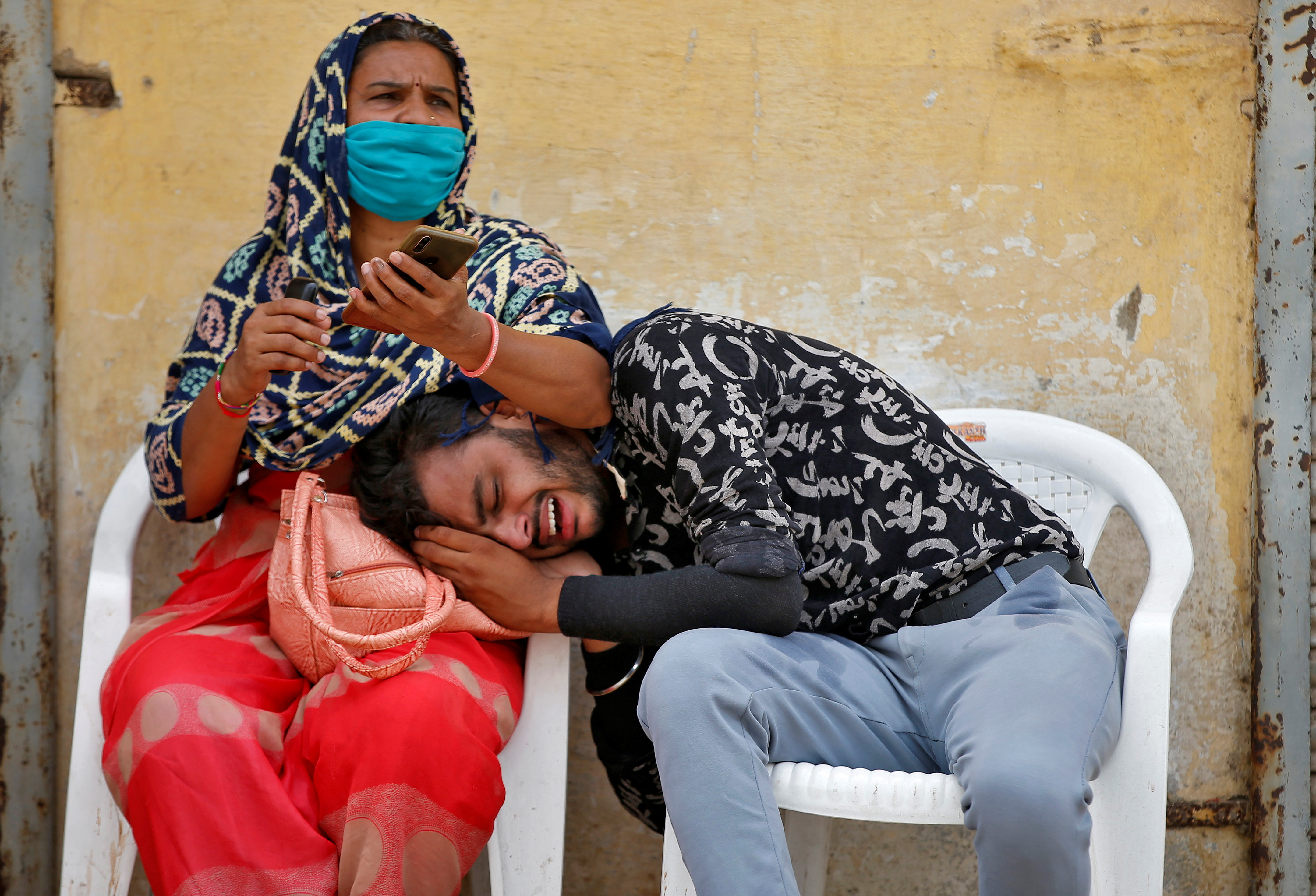 A man mourns after his father died due to the coronavirus disease (COVID-19) outside a mortuary of a COVID-19 hospital in Ahmedabad, India, May 8, 2021. REUTERS/Amit Dave