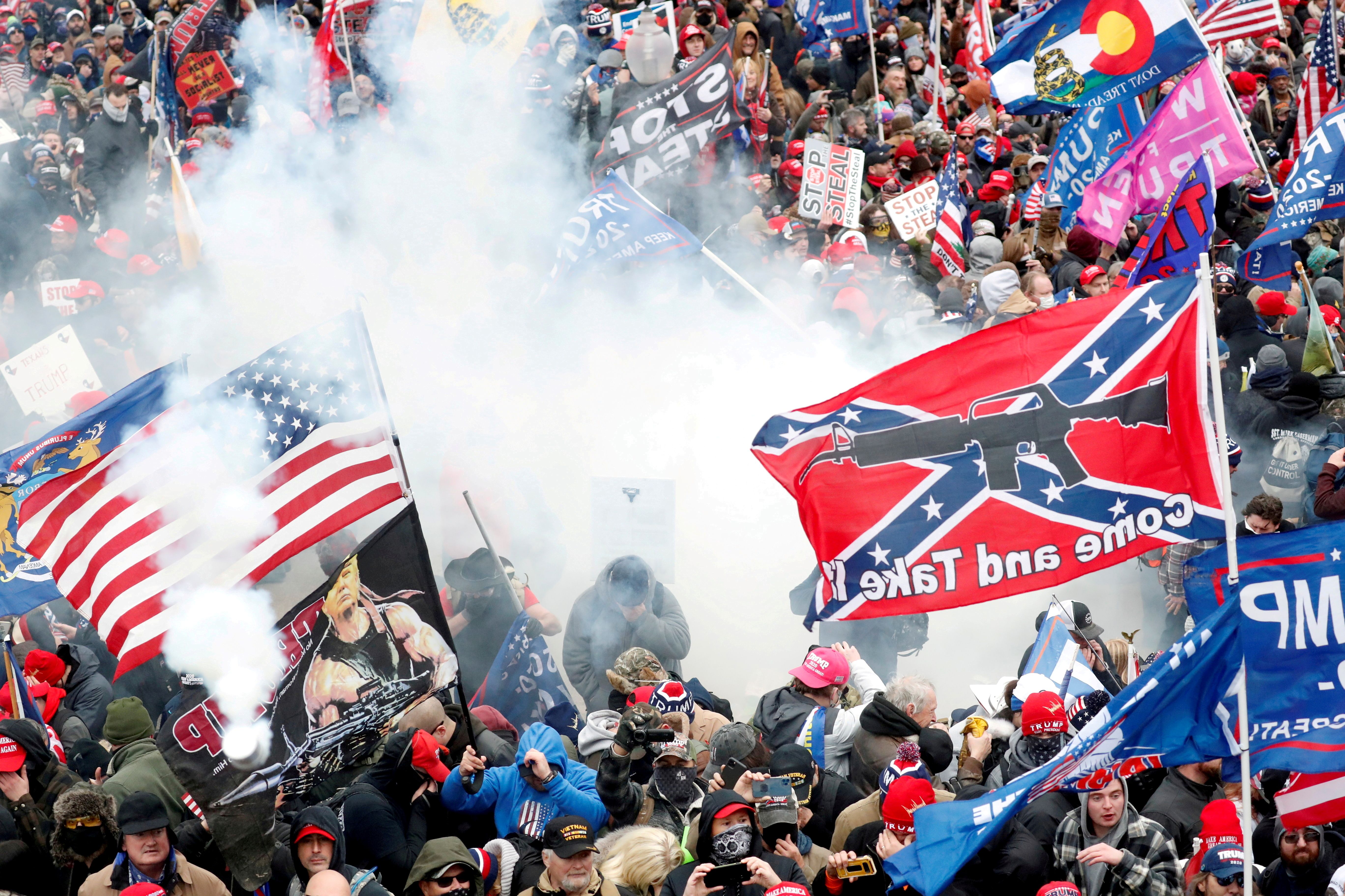 Tear gas is released into a crowd of protesters, with one wielding a Confederate battle flag that reads