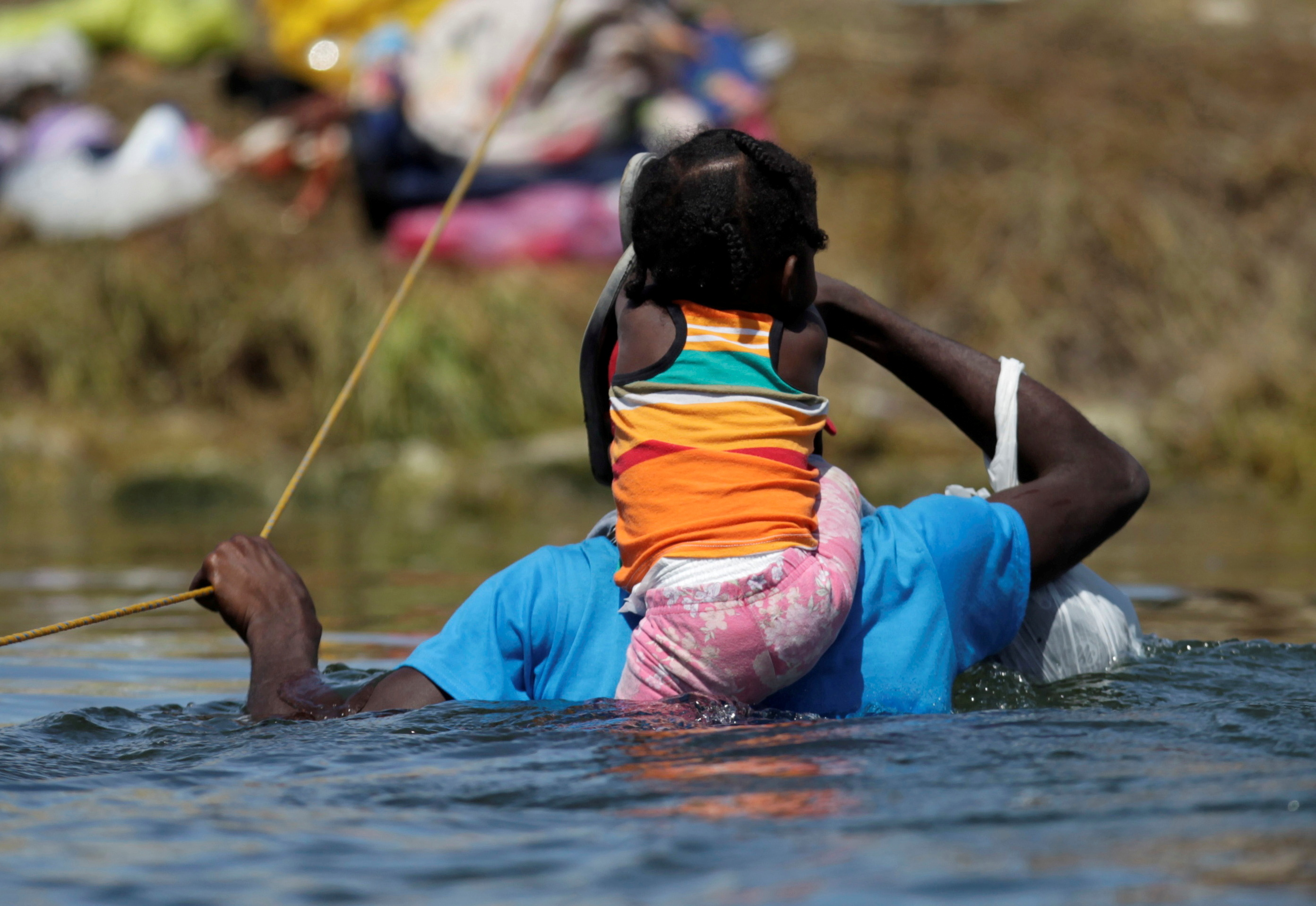 A migrant with a child seeking refuge in the U.S. wades through the Rio Grande from Ciudad Acuna, Mexico toward Del Rio, Texas, U.S., in Ciudad Acuna, Mexico September 22, 2021. REUTERS/Daniel Becerril