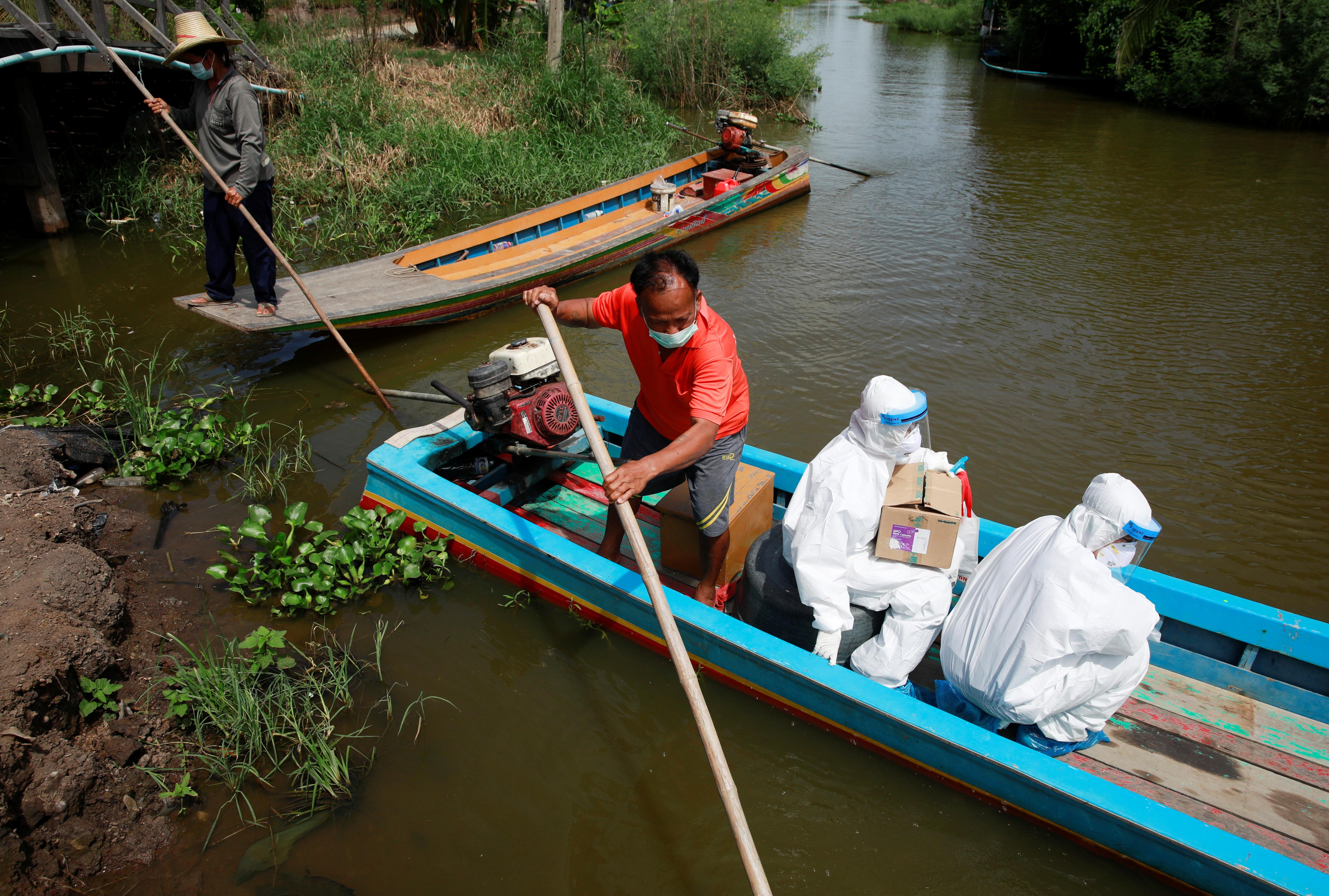 Public health officers Charoenrat Chaibut and Jurairat Tasom travel by boat to bring coronavirus disease (COVID-19) swab testing to residents living in remote communities, amid the rise of coronavirus disease infections, in Samut Prakan, near Bangkok, Thailand, July 19, 2021. REUTERS/Soe Zeya Tun