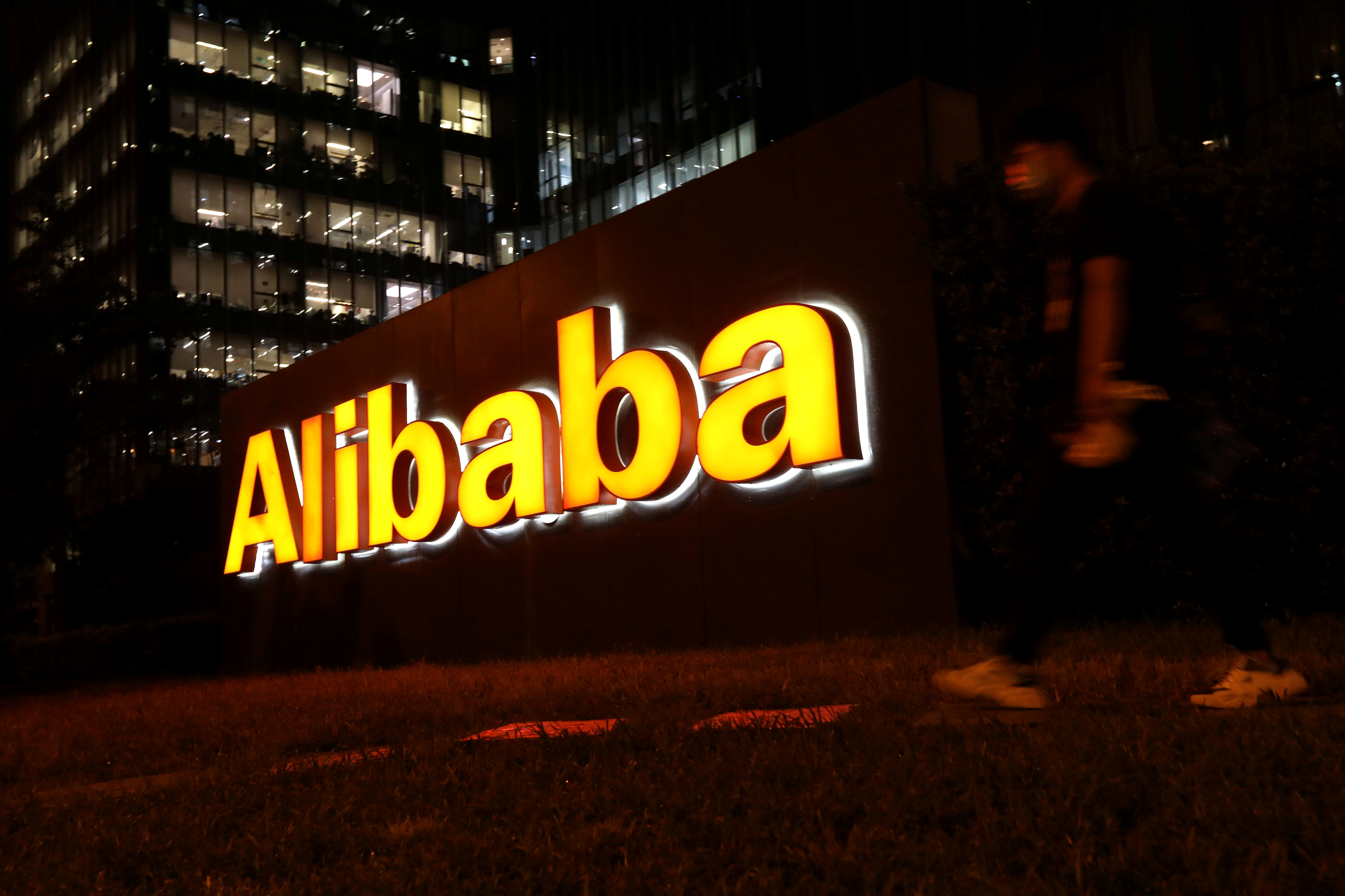 A man walks past a logo of Alibaba Group at its office building in Beijing, China August 9, 2021. REUTERS/Tingshu Wang