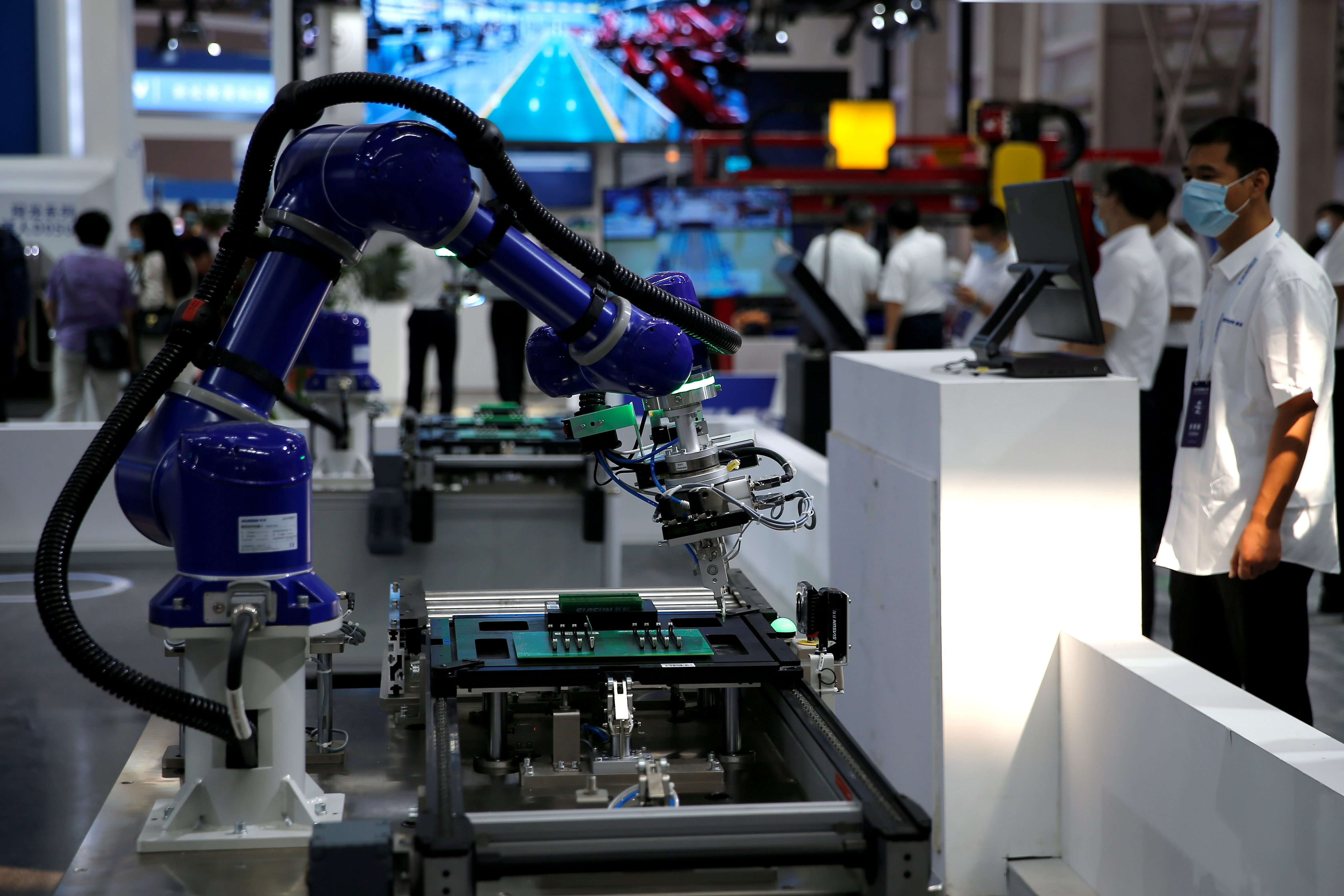 A robotic arm by Siasun operates for display at the Beijing World Robot Conference 2021 in Beijing, China September 10, 2021. REUTERS/Tingshu Wang/File Photo