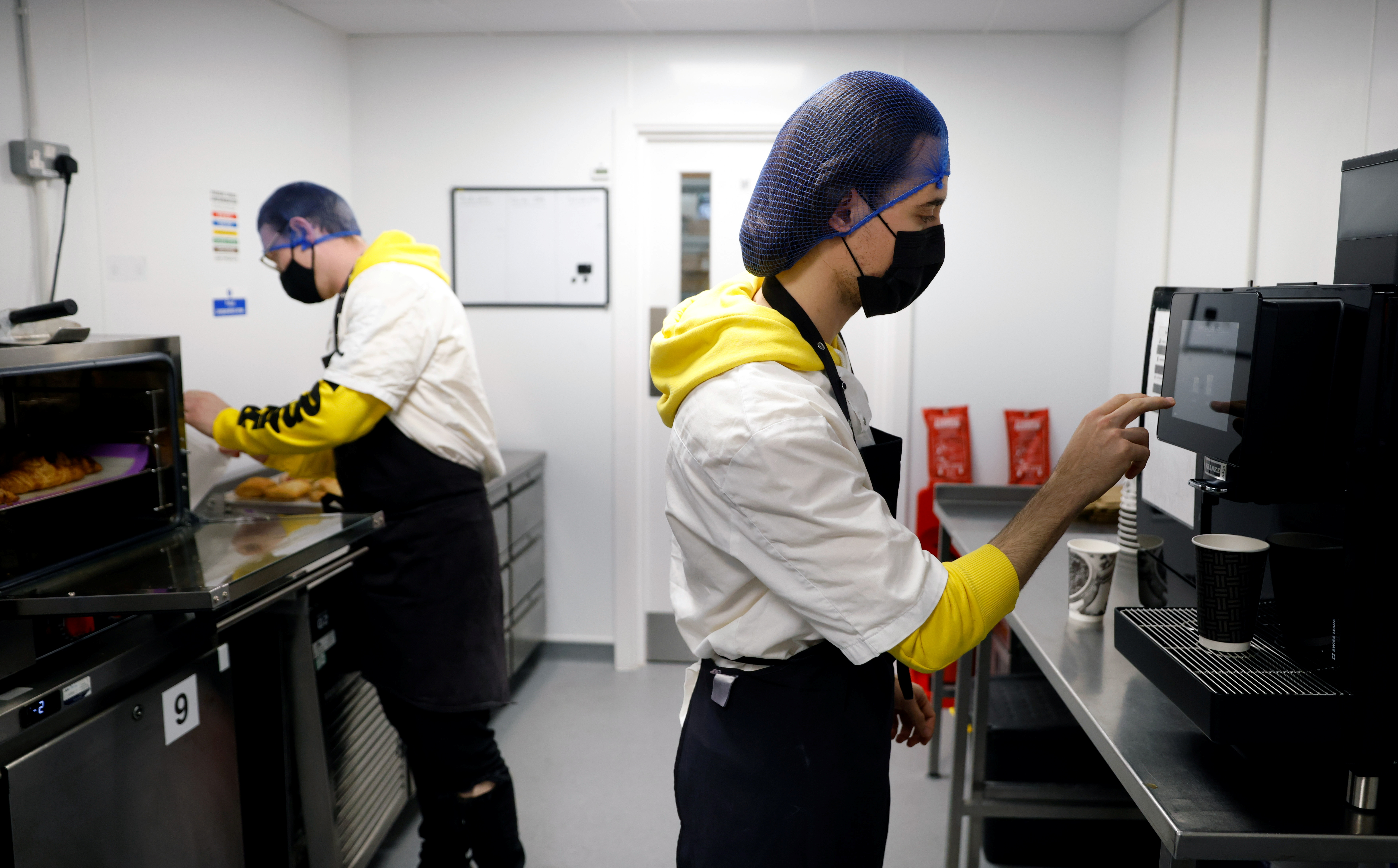 Yango Deli staff members prepare coffee and hot food for test deliveries in the kitchen prior to the opening of their new store in London, Britain, October 6, 2021. Picture taken October 6, 2021. REUTERS/John Sibley