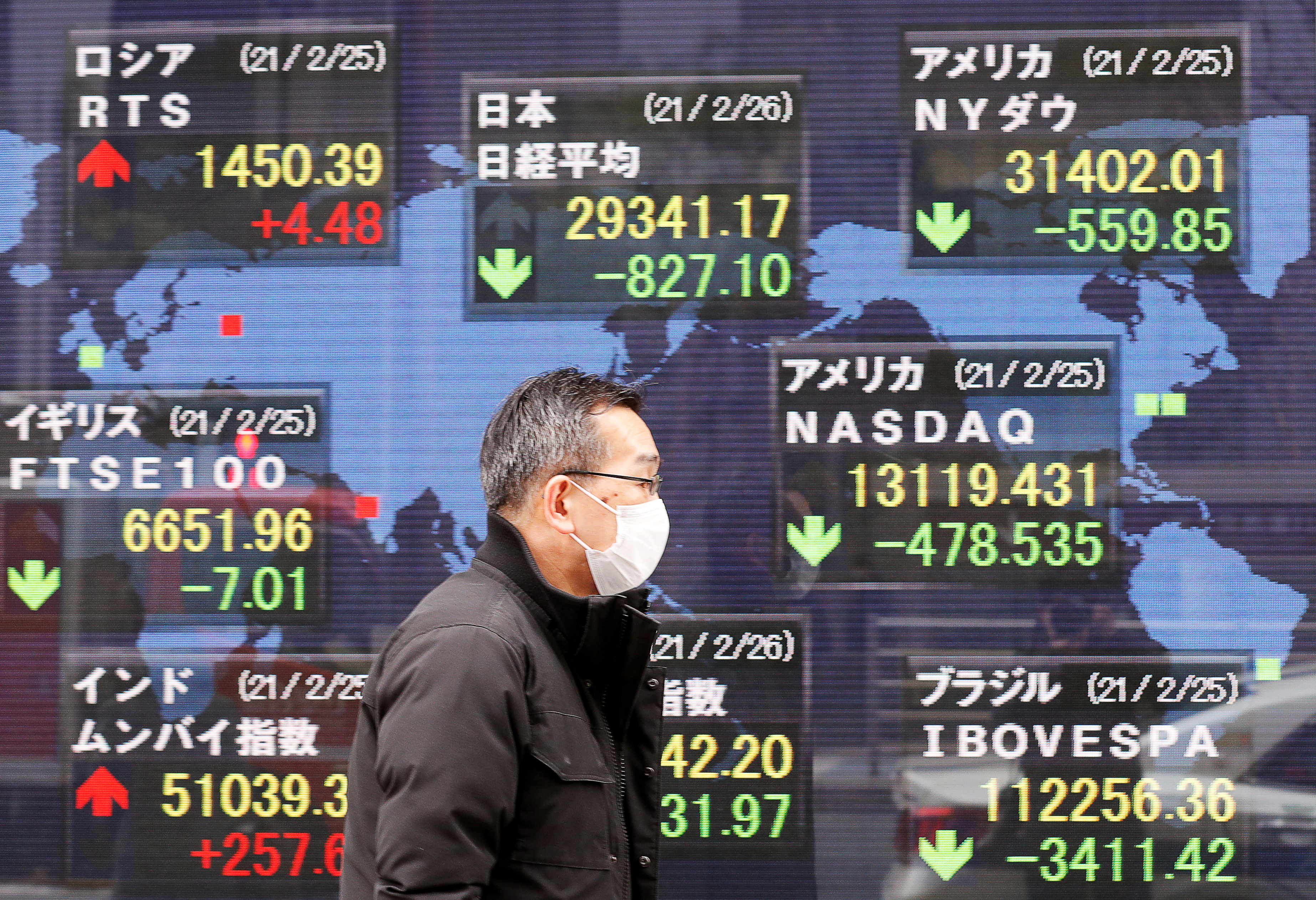 A man walks past a stock quotation board at a brokerage in Tokyo, Japan February 26, 2021. REUTERS/Kim Kyung-Hoon