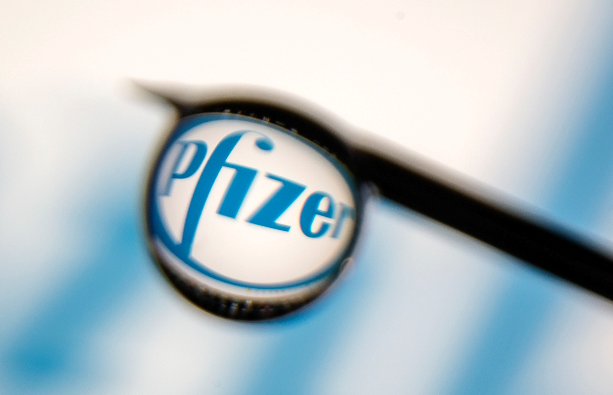Pfizer logo is reflected in a drop on a syringe needle in this illustration photo taken March 16, 2021. REUTERS/Dado Ruvic/Illustration