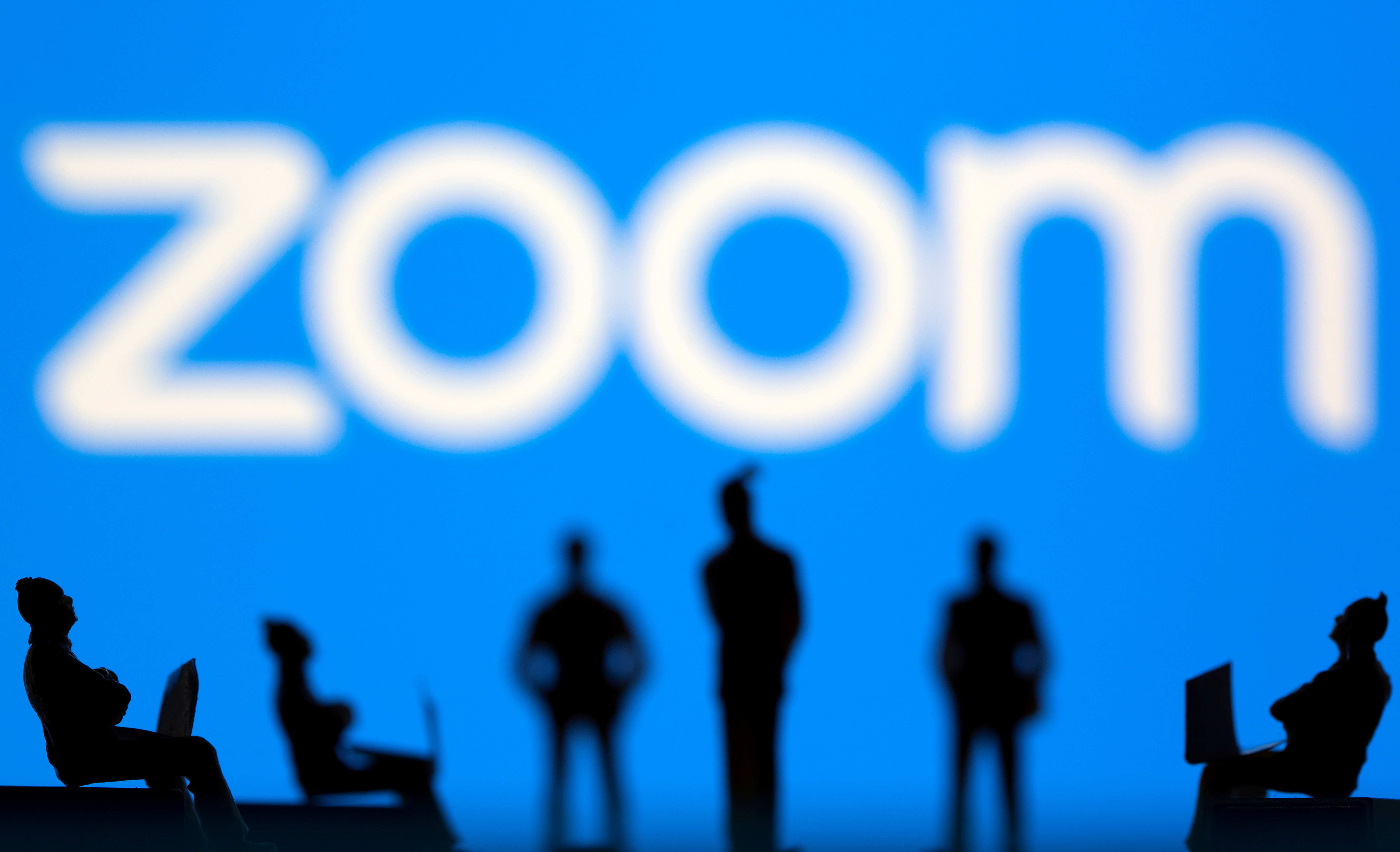 Small toy figures are seen in front of Zoom logo in this illustration picture taken March 15, 2021. REUTERS/Dado Ruvic/Illustration/File Photo