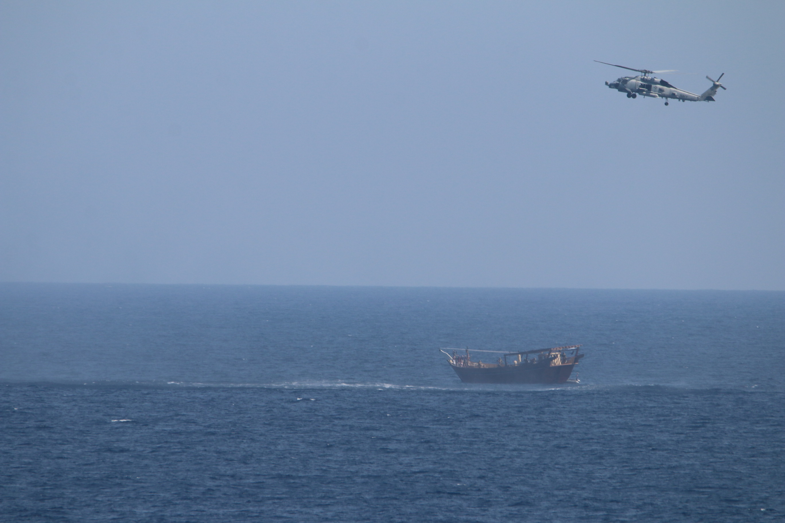 An SH-60 Seahawk helicopter assigned to the United States guided-missile cruiser USS Monterey (CG 61)(not shown) flies above a stateless dhow interdicted with a shipment of illicit weapons in international waters of the North Arabian Sea in this picture taken on May 6, 2021 and released by U.S.Navy on May 9, 2021. U.S. Navy Forces Central Command/U.S. Navy/Handout via REUTERS