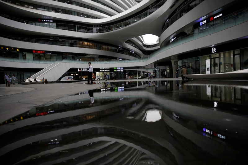A member of security personnel wearing a face mask stands guard as the Galaxy SOHO office and commercial buildings are reflected in the water, following the novel coronavirus disease (COVID-19) outbreak, in Beijing, China June 1, 2020. REUTERS/Tingshu Wang