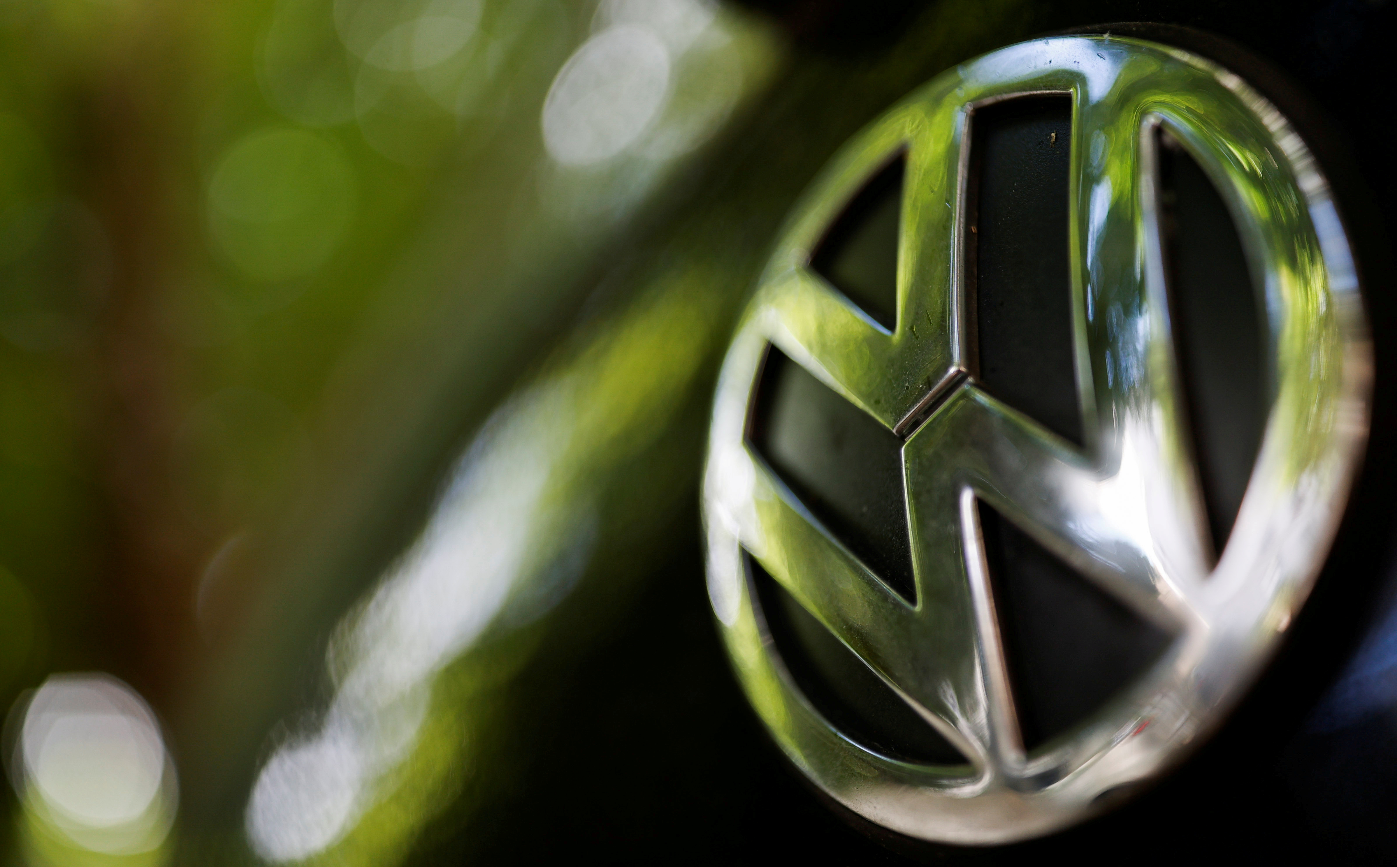 A logo of German carmaker Volkswagen is seen on a car parked on a street in Paris, France, July 9, 2020. REUTERS/Christian Hartmann/File Photo