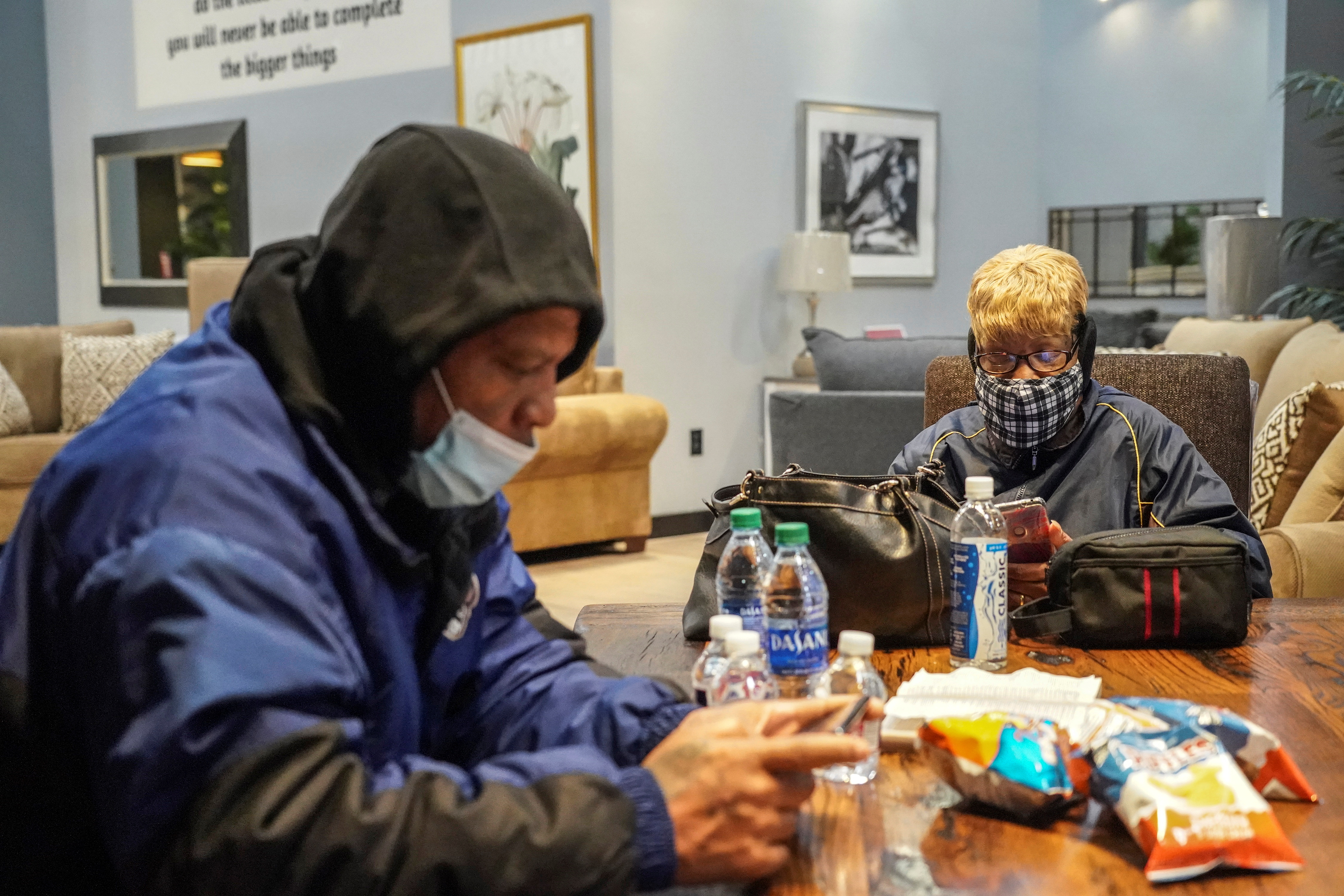 Jason Miszell (L) and his wife Debra Bracey check their smartphones while taking a shelter at Gallery Furniture store which opened its door and transformed into a warming station after winter weather caused electricity blackouts in Houston, Texas, U.S. February 17, 2021.  REUTERS/Go Nakamura