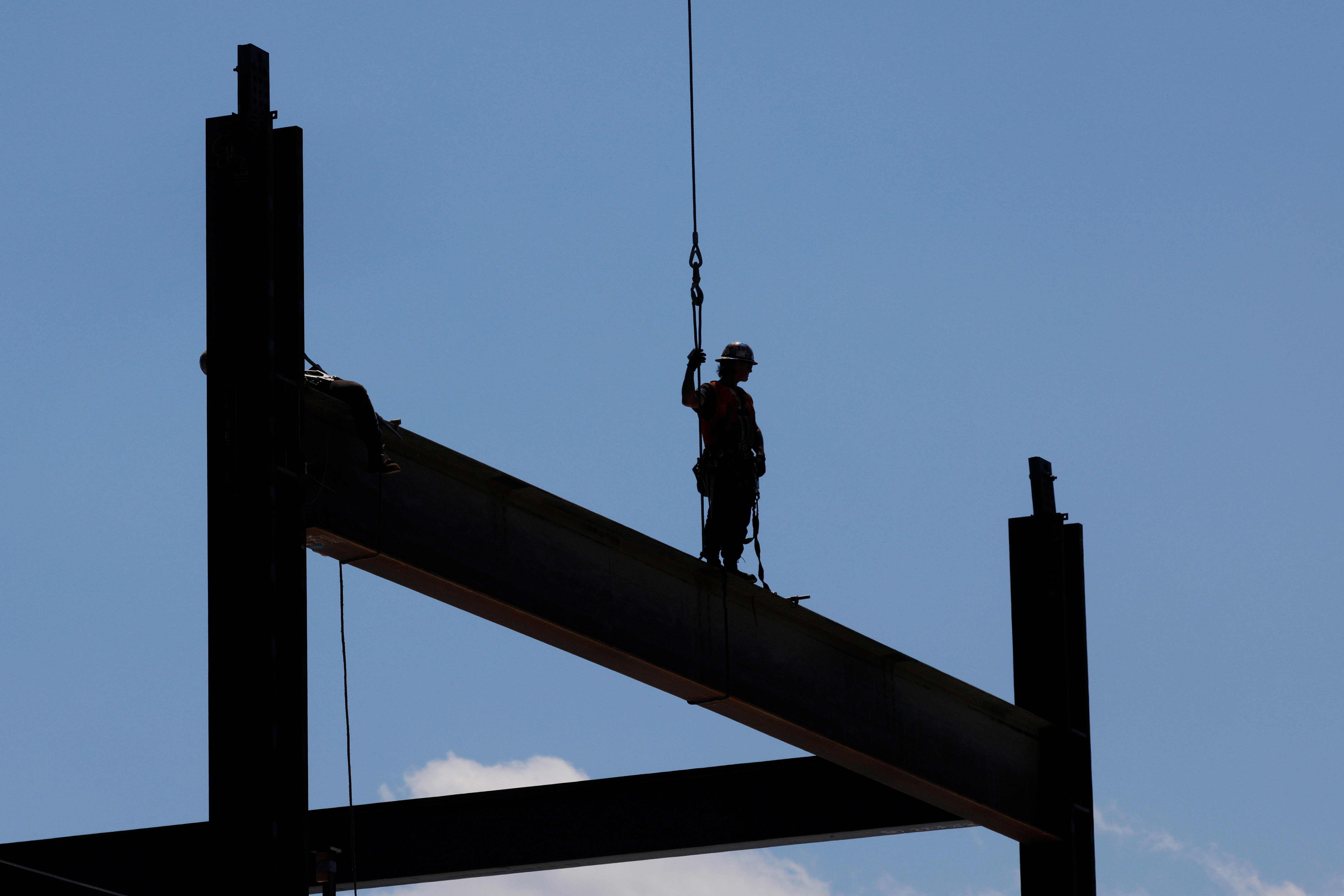 A member of the Ironworkers Local 7 union installs steel beams on high-rise building under construction during a summer heat wave in Boston, Massachusetts, U.S., June 30, 2021.   REUTERS/Brian Snyder