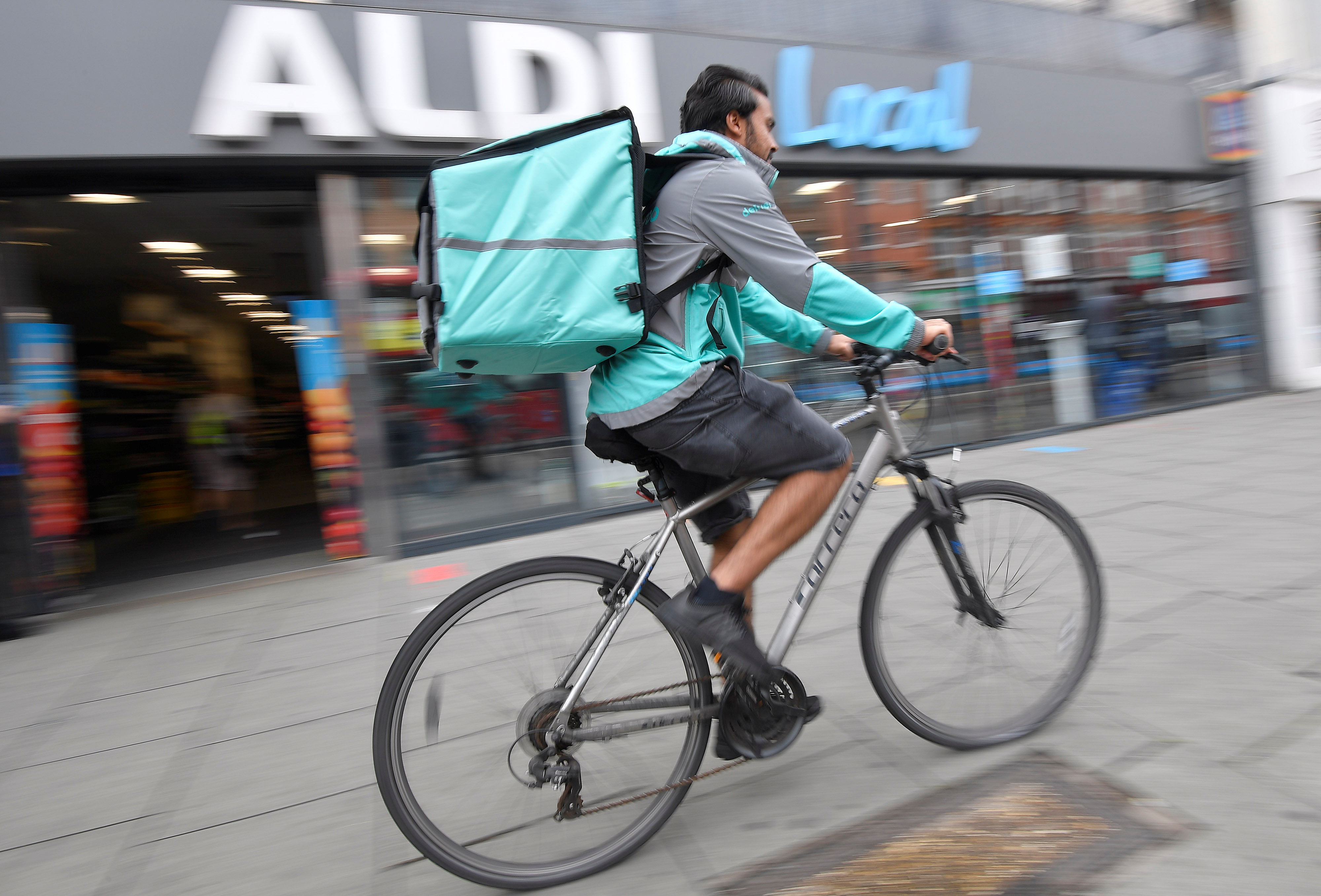 Abdelaziz Abdou, a Deliveroo delivery rider, poses with a bag of Aldi groceries, as discount supermarket chains Aldi and Lidl look poised to accelerate their push into home delivery to satisfy burgeoning demand for online grocery shopping in a shift expected to endure beyond the coronavirus crisis, in London, Britain, June 17, 2020. Picture taken June 17, 2020. REUTERS/Toby Melville